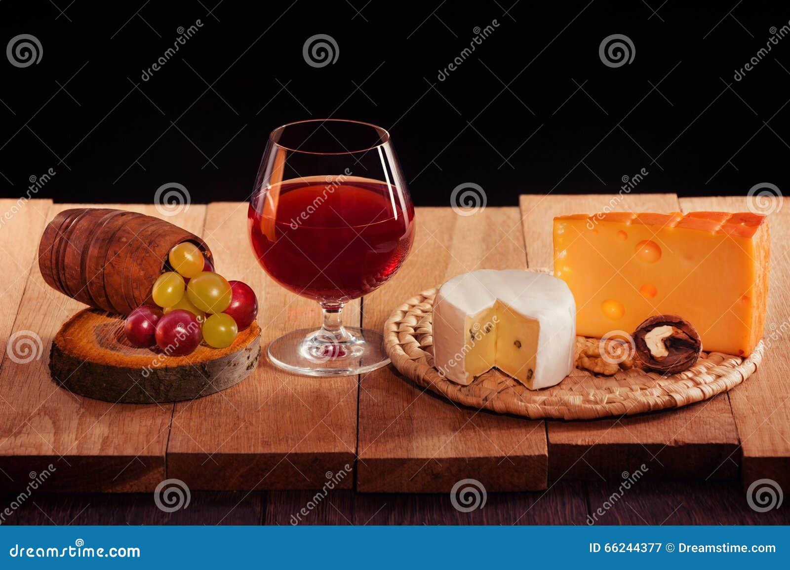 Ett exponeringsglas av rött vin med ost, druvor och muttrar