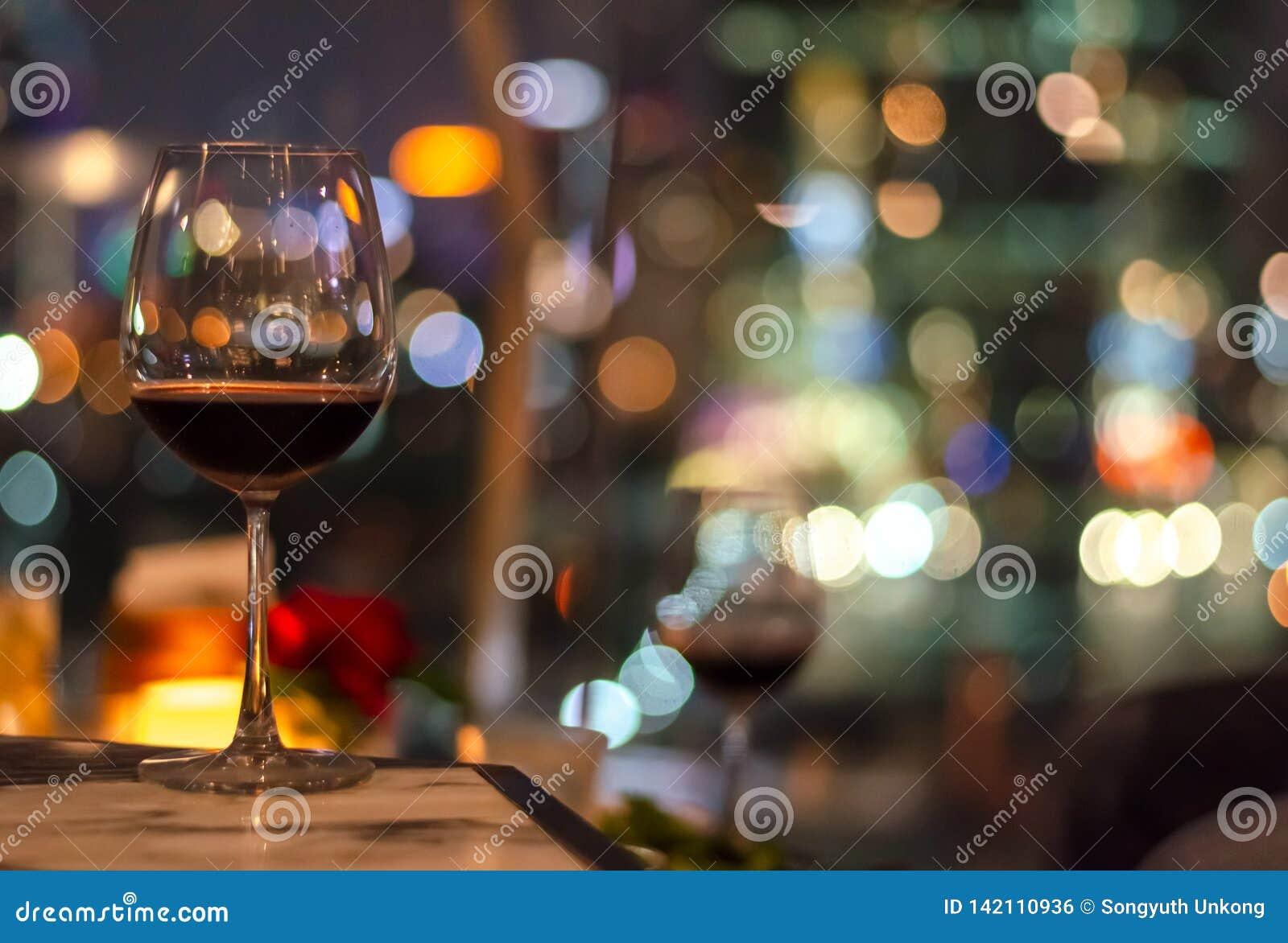 Ett exponeringsglas av rött vin på tabellen av takstången