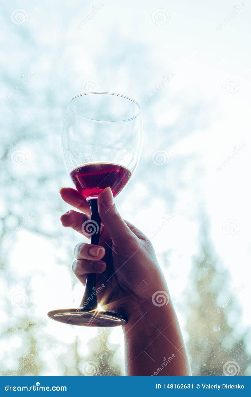 Ett exponeringsglas av r?tt vin i h?nderna av en flicka
