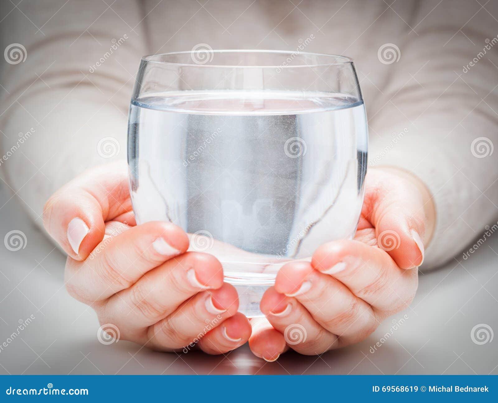 Ett exponeringsglas av ren mineralvatten i kvinnas händer Miljöskydd, sund drink