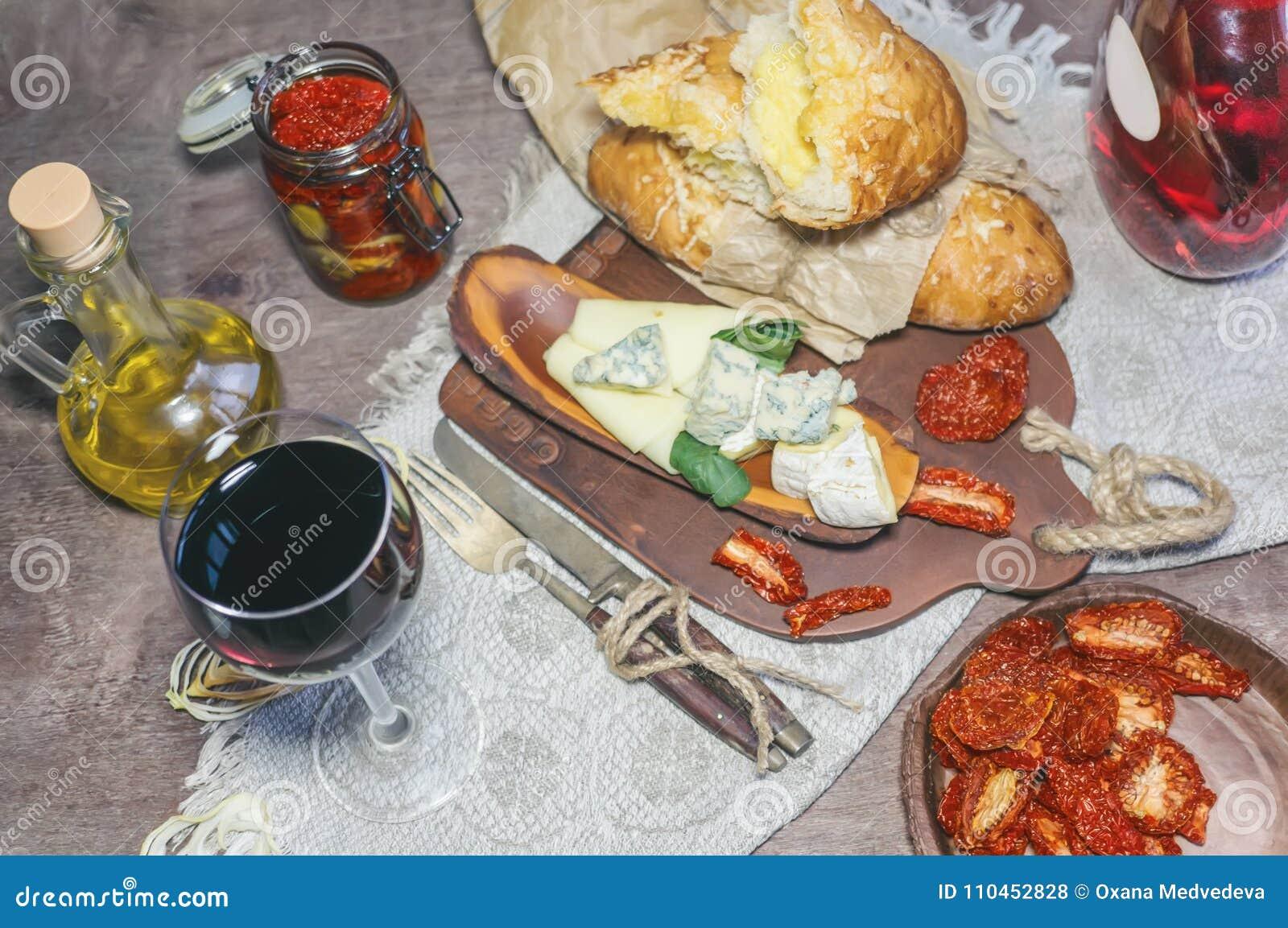 Ett exponeringsglas av torrt rött vin- och italienareFocaccia bröd med ost och ett ostuppläggningsfat med fikonträd och Gorgonzol