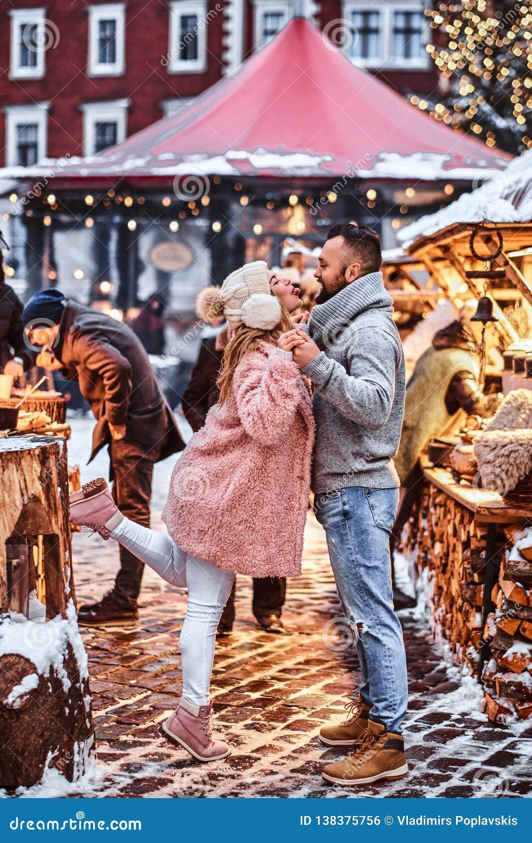 Ett förälskat attraktivt par och att ha gyckel tillsammans på en julmässa