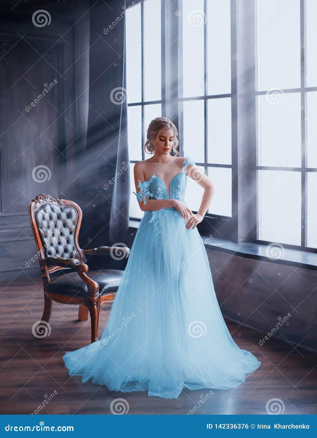 Ett försiktigt, snödrottningställningar vid fönstret i en sagolik klänning med kala skuldror Rummet fylls med magiska strålar
