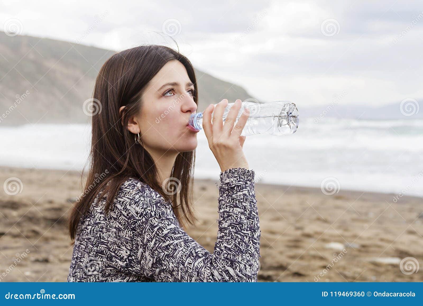 Ett flickadricksvatten i stranden