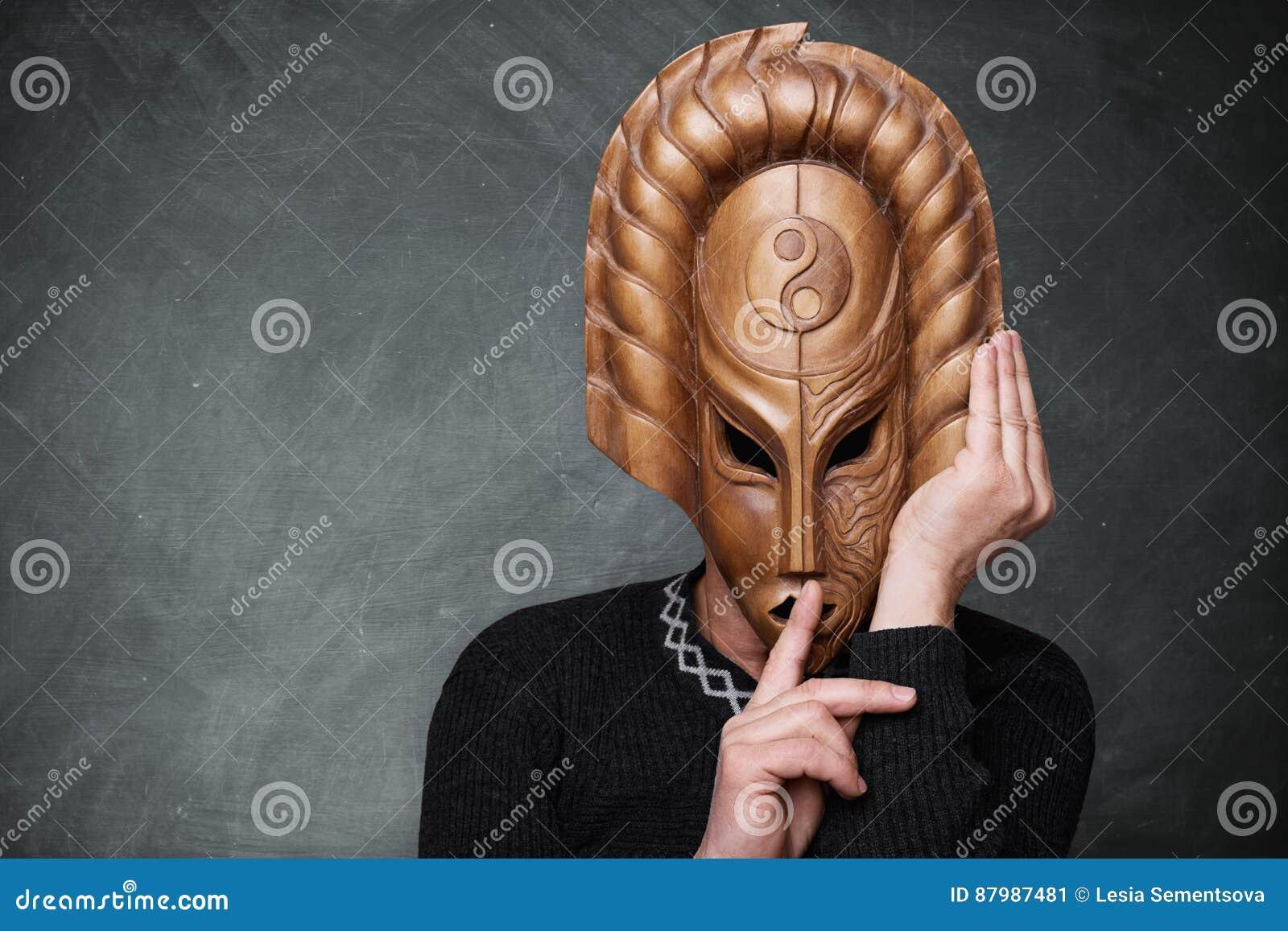 Ett foto av mannen som står yang för yin för near bakgrund för kritabräde som den bärande maskeringen visar tecknet av tystnad En