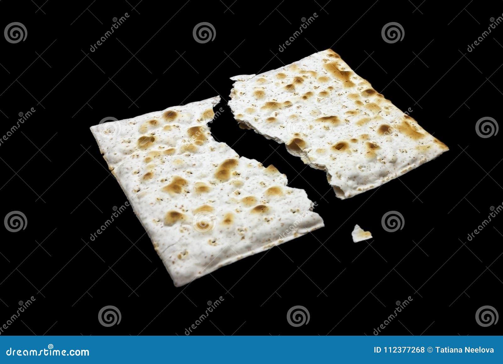 Ett foto av två stycken av matzah eller matza som isoleras på svart bakgrund Matzah för de judiska påskhögtidferierna Ställe för