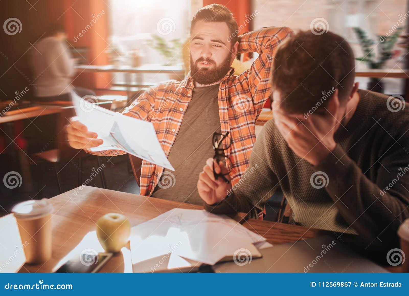 Ett foto mycket av förtvivlan Två vänner, som arbetar tillsammans, studerar diagram det hårt till undertand De har att vara