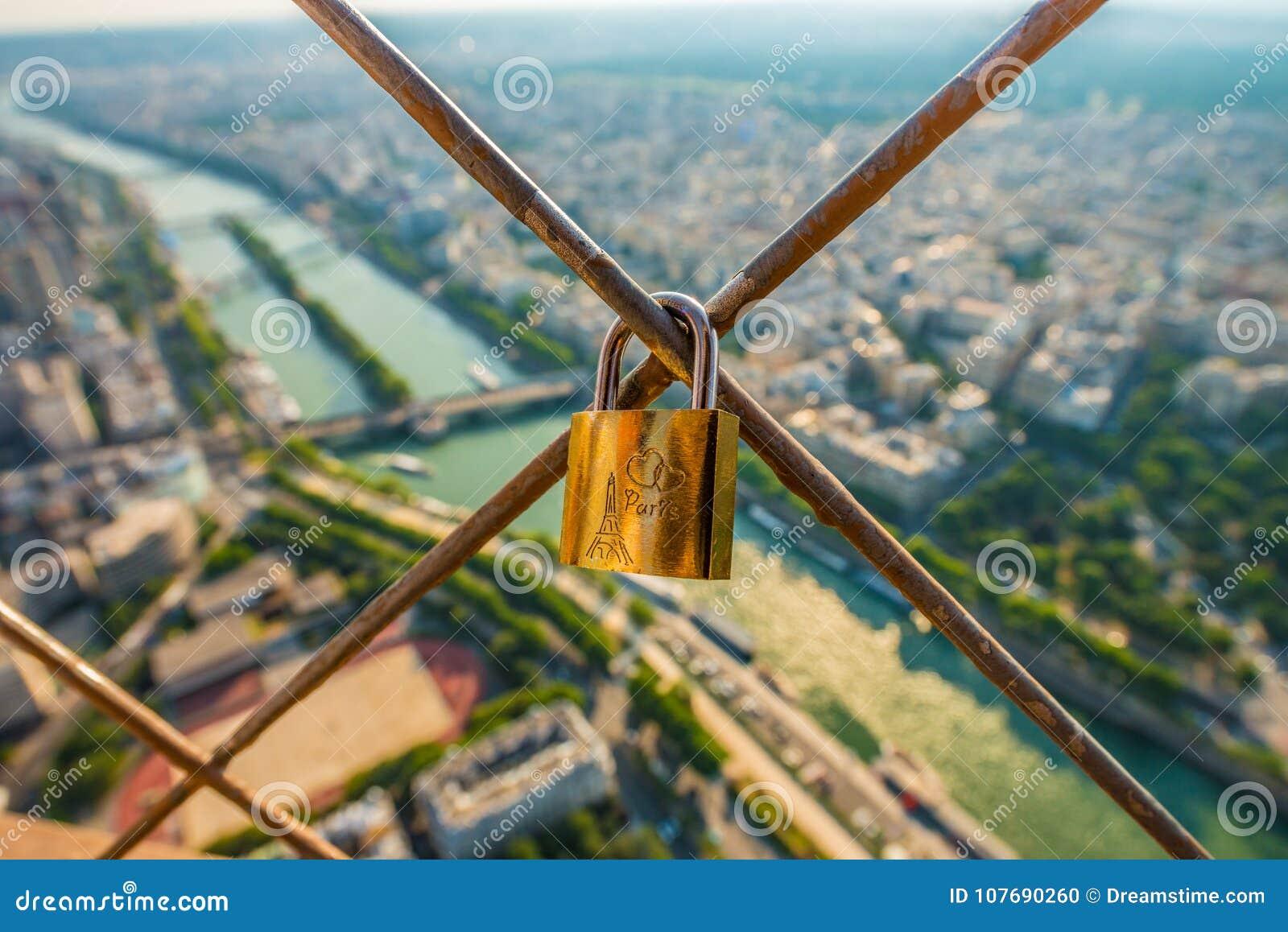 Ett guld- lås som förläggas på ett staket av Eiffeltorn som ser över floden Seine