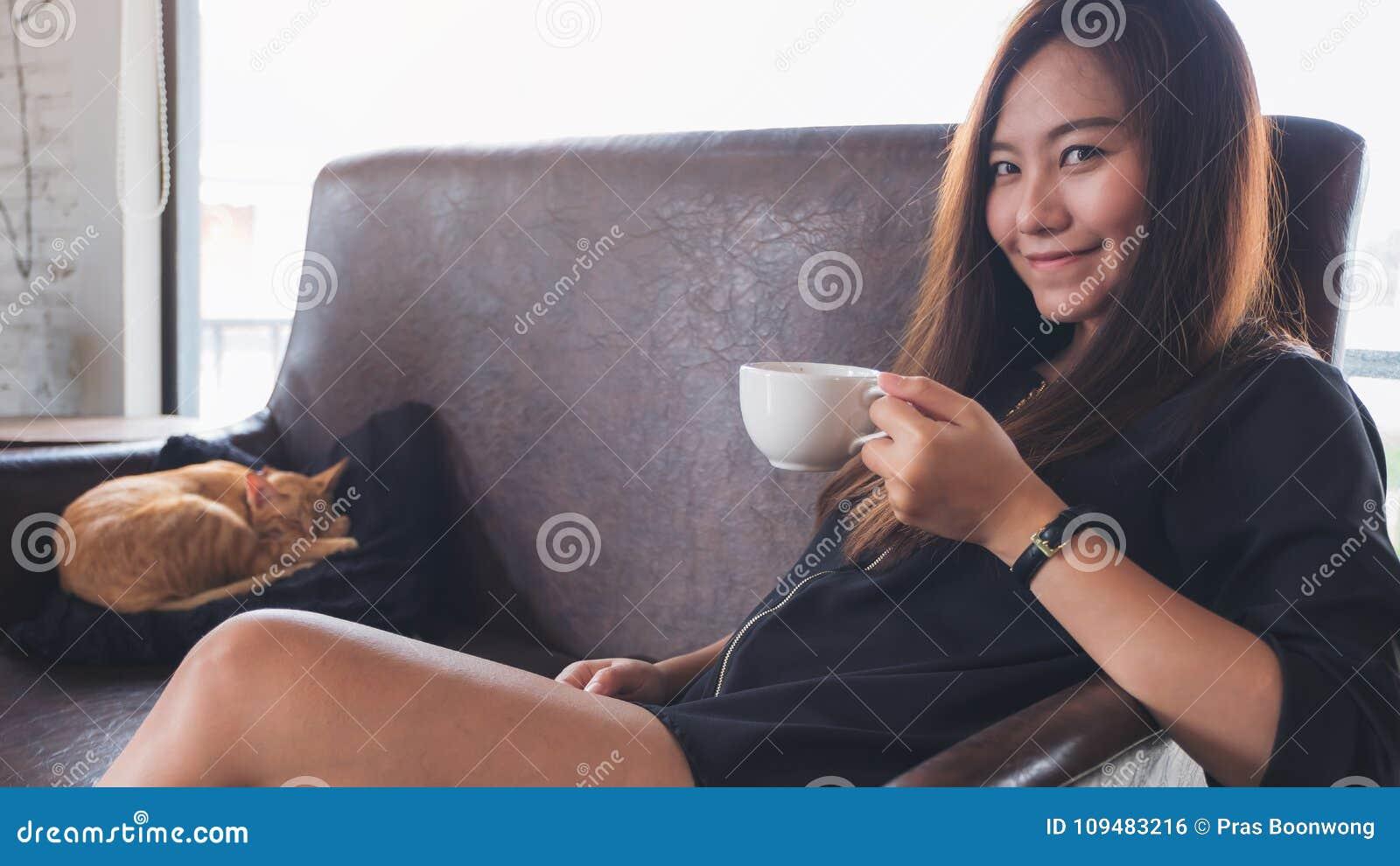 Ett härligt asiatiskt kvinnasammanträde på soffan, medan lite den bruna katten sover på en svart kudde