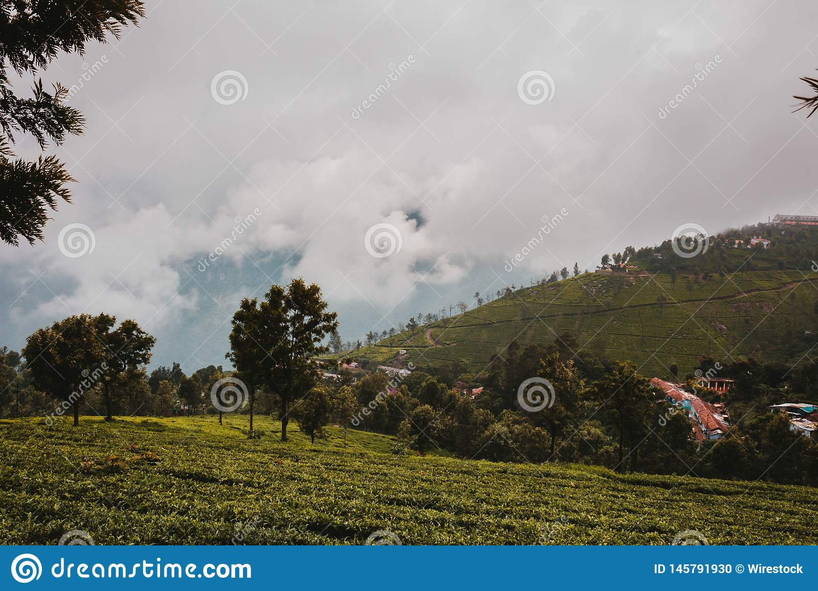 Ett härligt grönt fält nära en liten stad och molniga himlar över kullarna