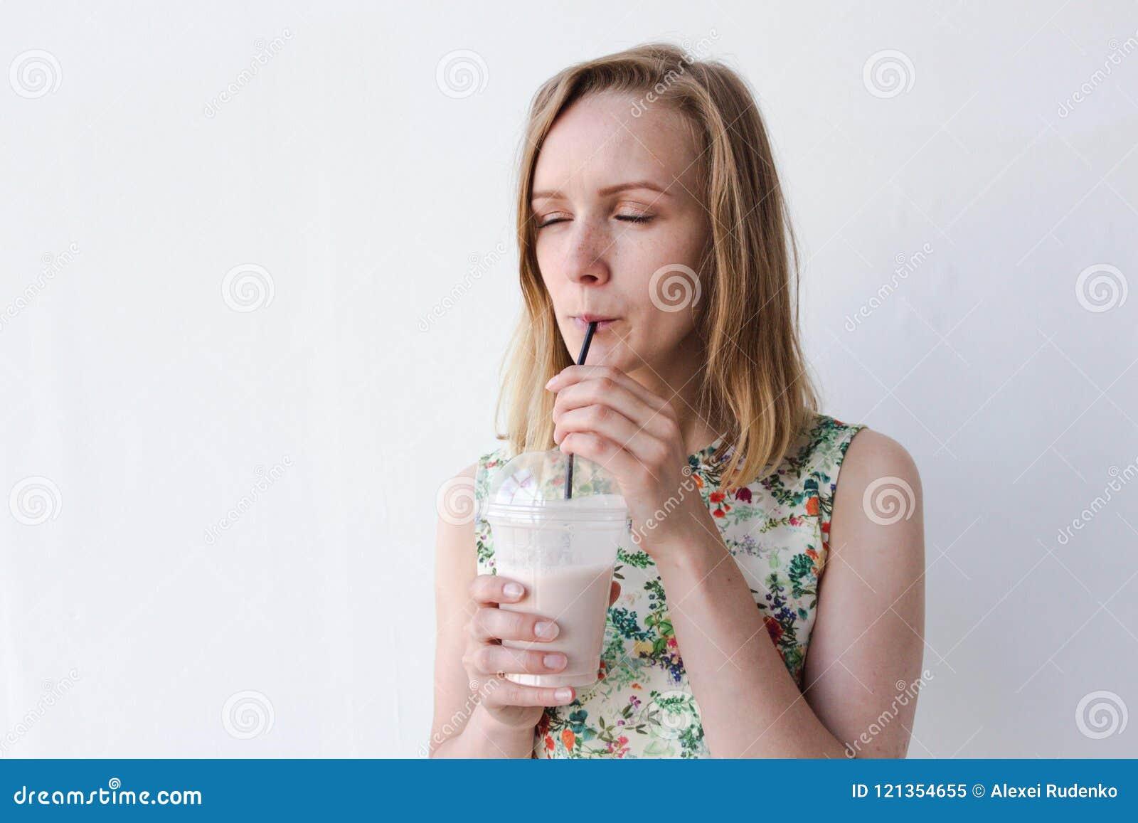 Ett härligt och en ung flicka står på en vit bakgrund och dricker en drink Hon är mycket glad och tycker om drinken Drinken är