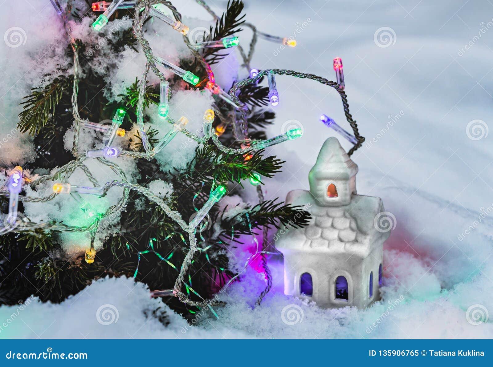 Ett härligt sagolikt litet vitt hus med gula och blåa ljus i fönstren och girlanderna av att bränna färgrika lampor på a