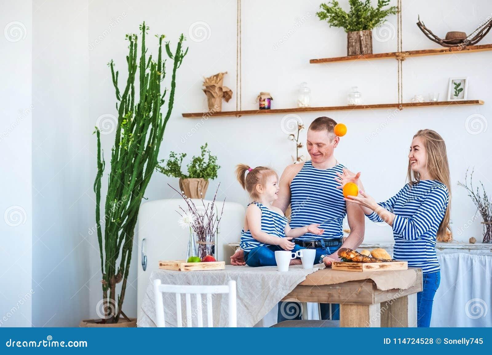 Ett härligt vårfoto av en lycklig familj i blå sommar tilldelar inre av köket i ljus texturerade färger med en ol
