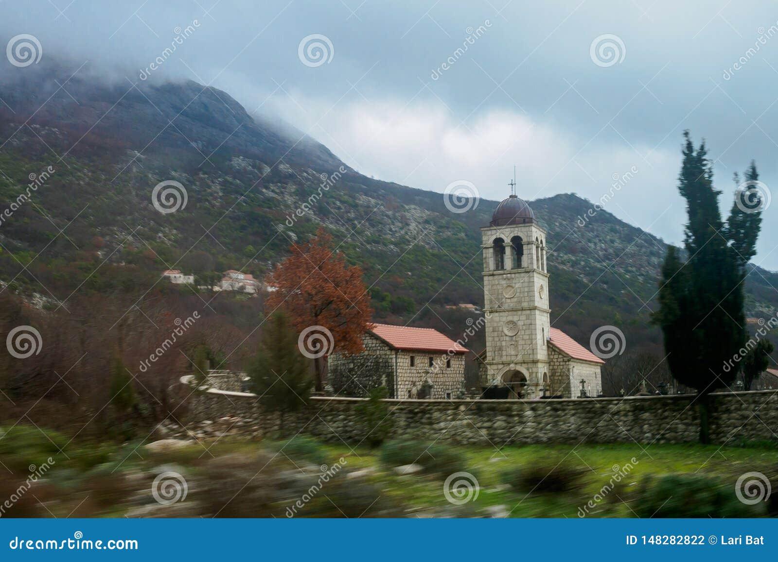 Ett kapell i en liten bykyrkogård bak ett staket i bakgrunden av berg i molnigt väder F?rgrunden ?r suddig