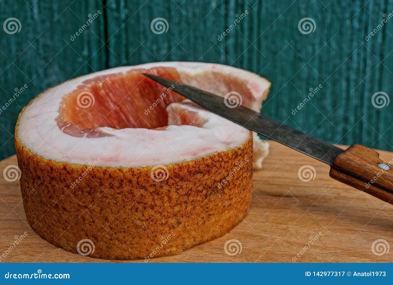 Ett långt stycke av nytt griskött späcker, och en kniv lägger på en brun träplanka mot en grön vägg