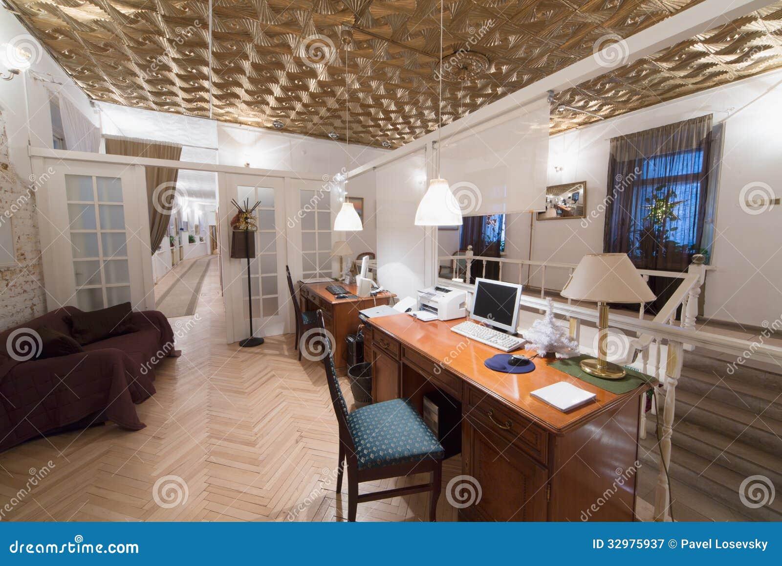 Ett litet rum med två skrivbord och en dörr royaltyfri fotografi ...