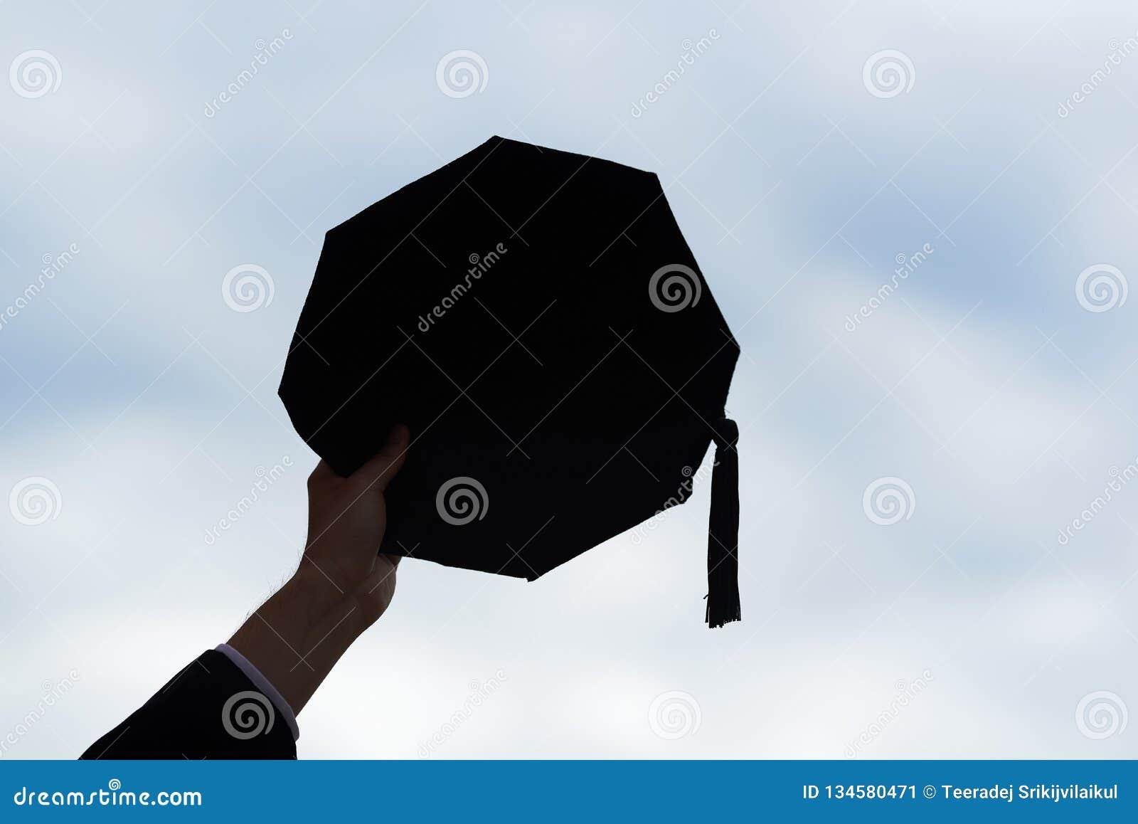 Ett lock för handinnehavavläggande av examen på bakgrund för blå himmel