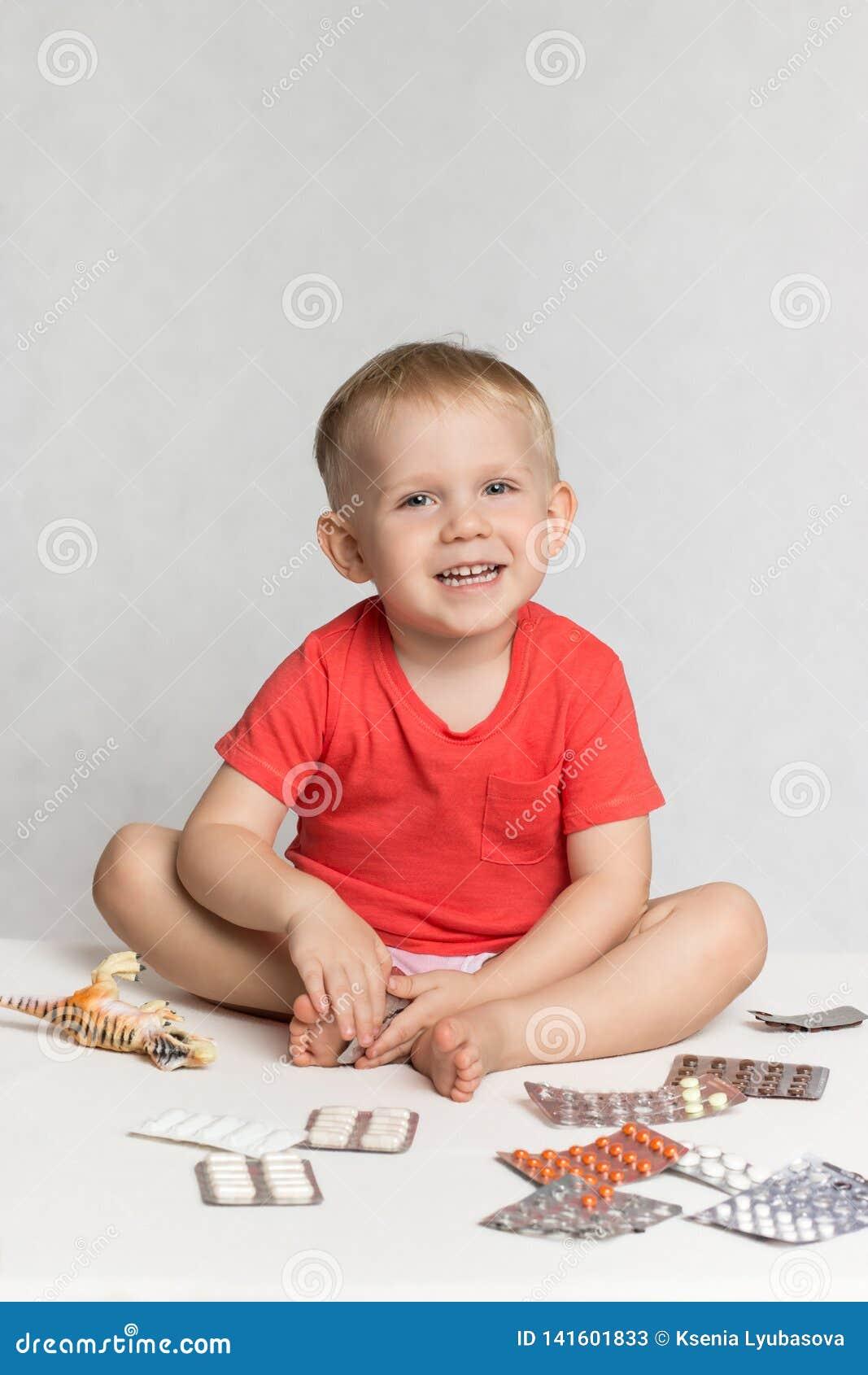 Ett lyckligt behandla som ett barn lilla barnet i en levande korallfärgT-tröja sitter bland pillren och drogerna