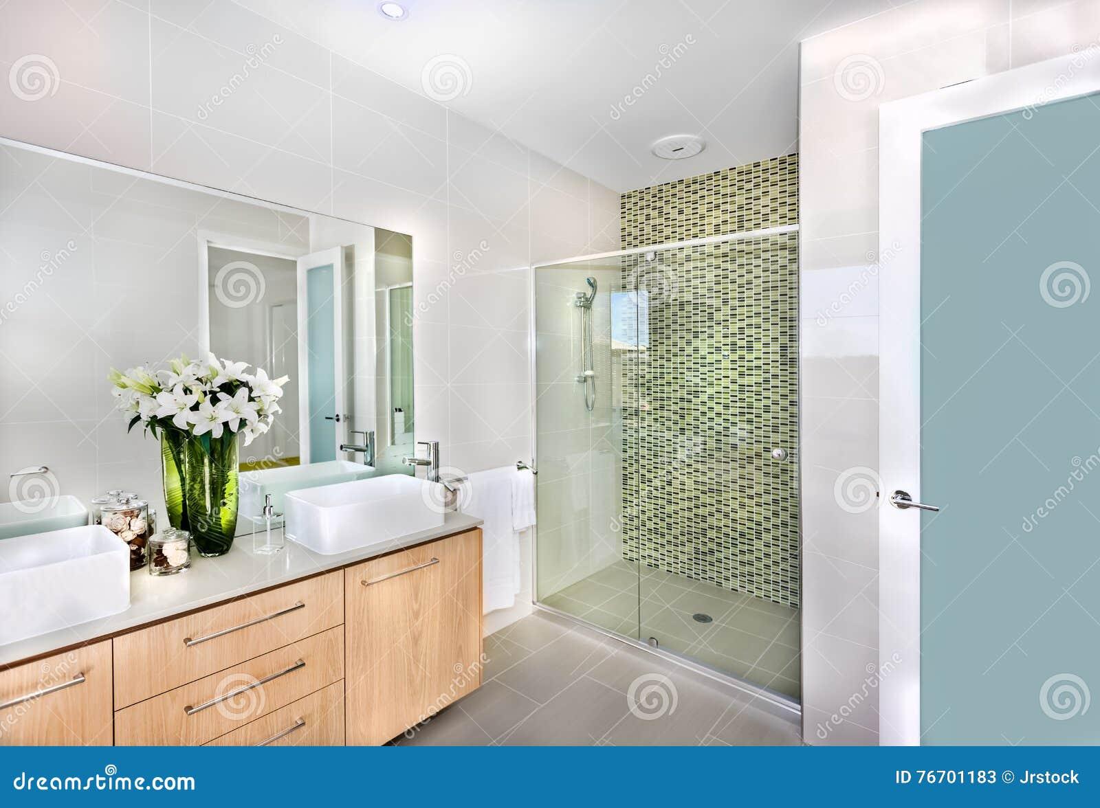 Ett modernt badrum med vita blommor i vasen