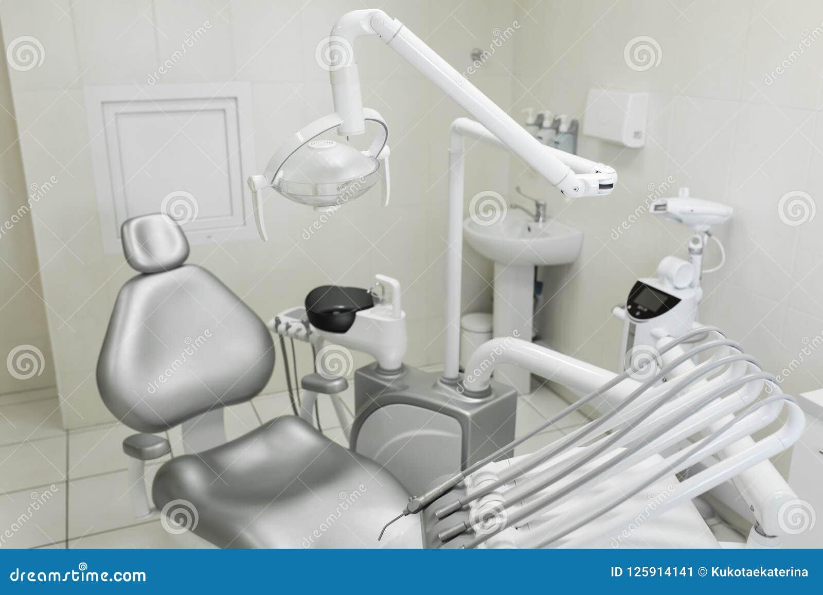 Ett modernt brunn-utrustat kontor för tandläkare` s, en tålmodig grå färgstol för ` s Maskin för att borra tänder och annan tand-