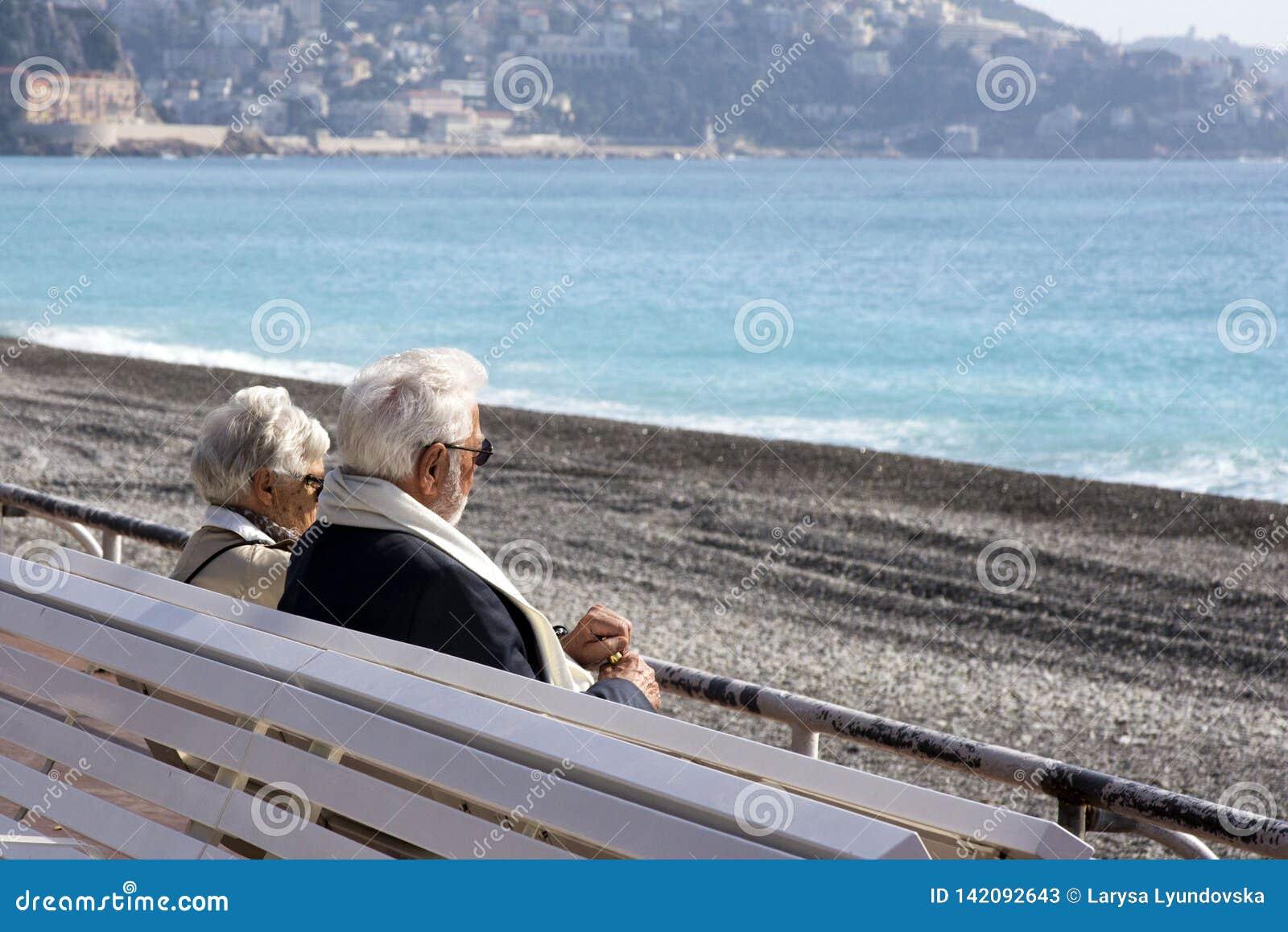 Ett moget gråhårigt härligt par: en man och en kvinna sitter på en vit bänk på Promenade des Anglais och ser