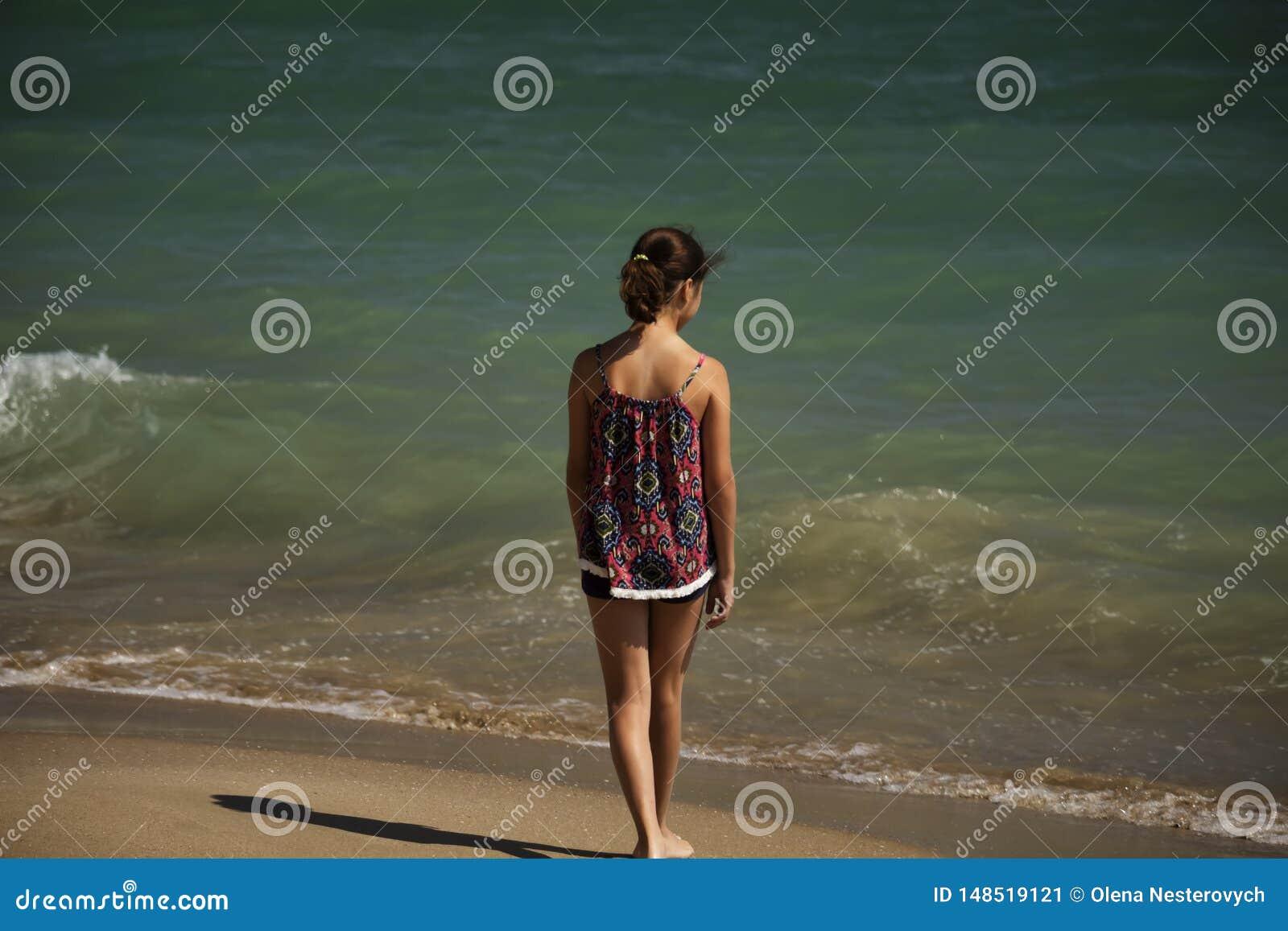 Ett n?tt flickaanseende p? stranden och se l?ngt in i havet, mjuk fockus
