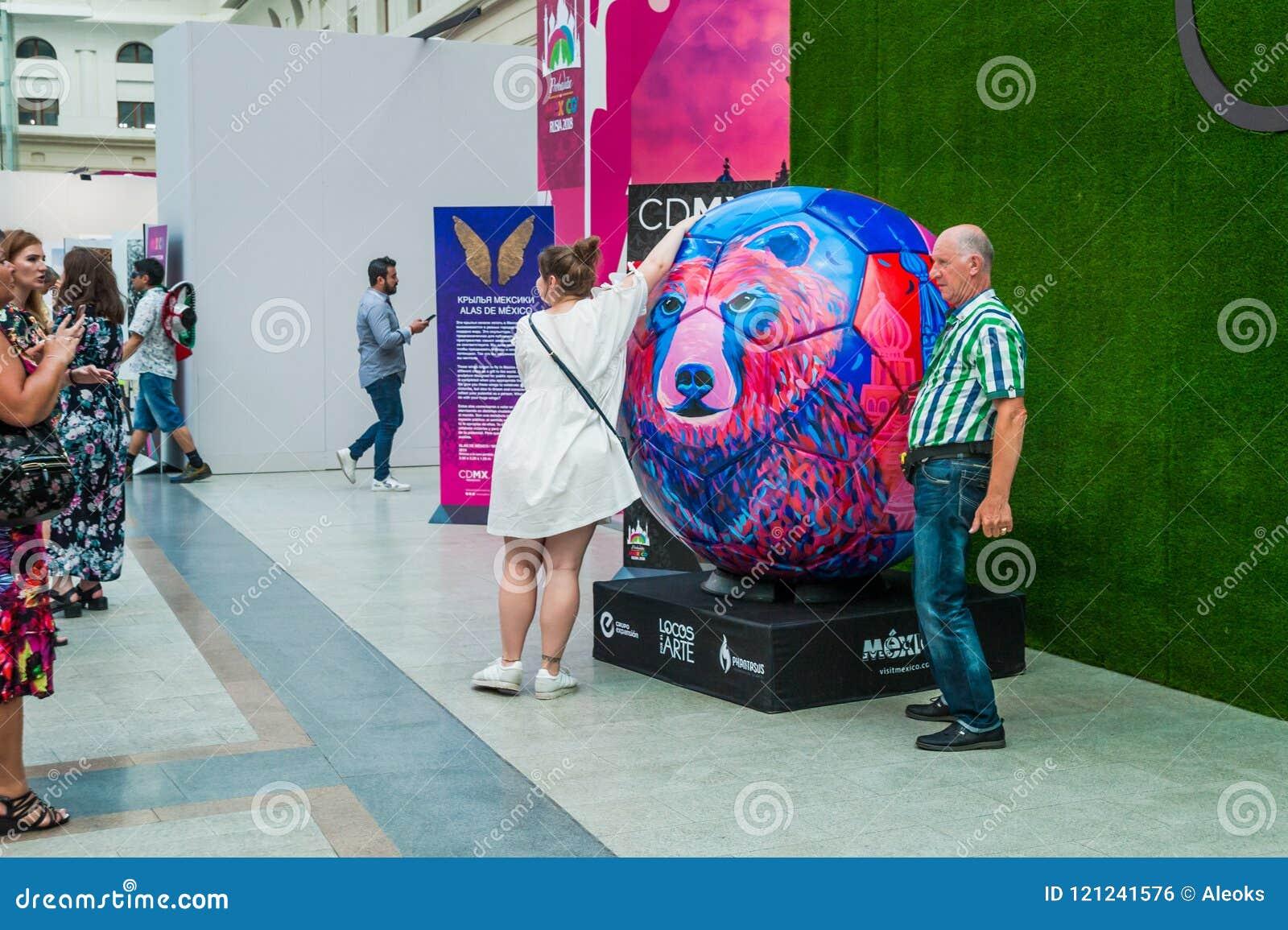 Ett nationellt hus för mexikan fläktar i Gostiny Dvor Folket fotograferas runt om en stiliserad fotbollboll med en björn