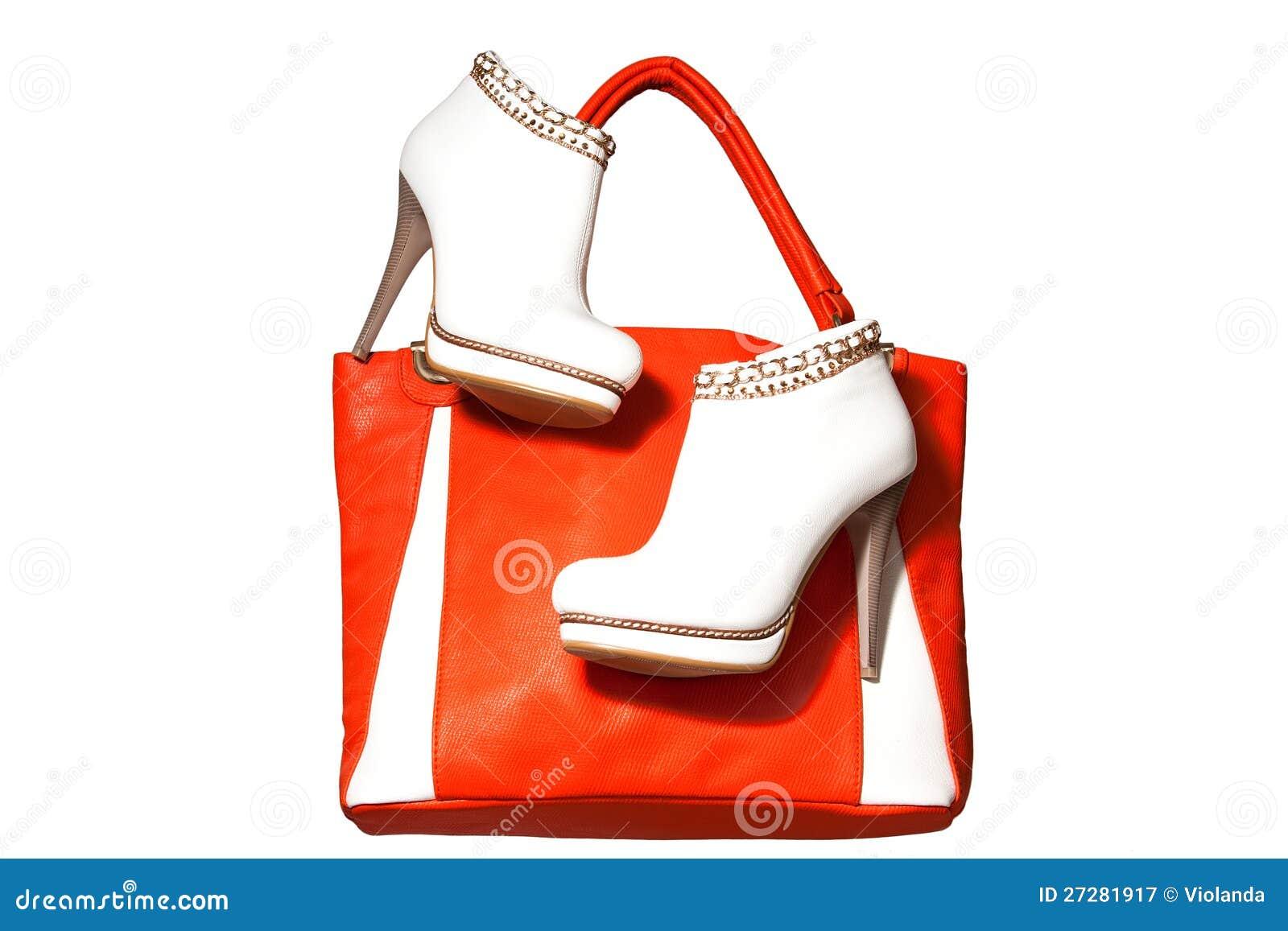 Ett par av kvinna den ankelkängor och handväskan