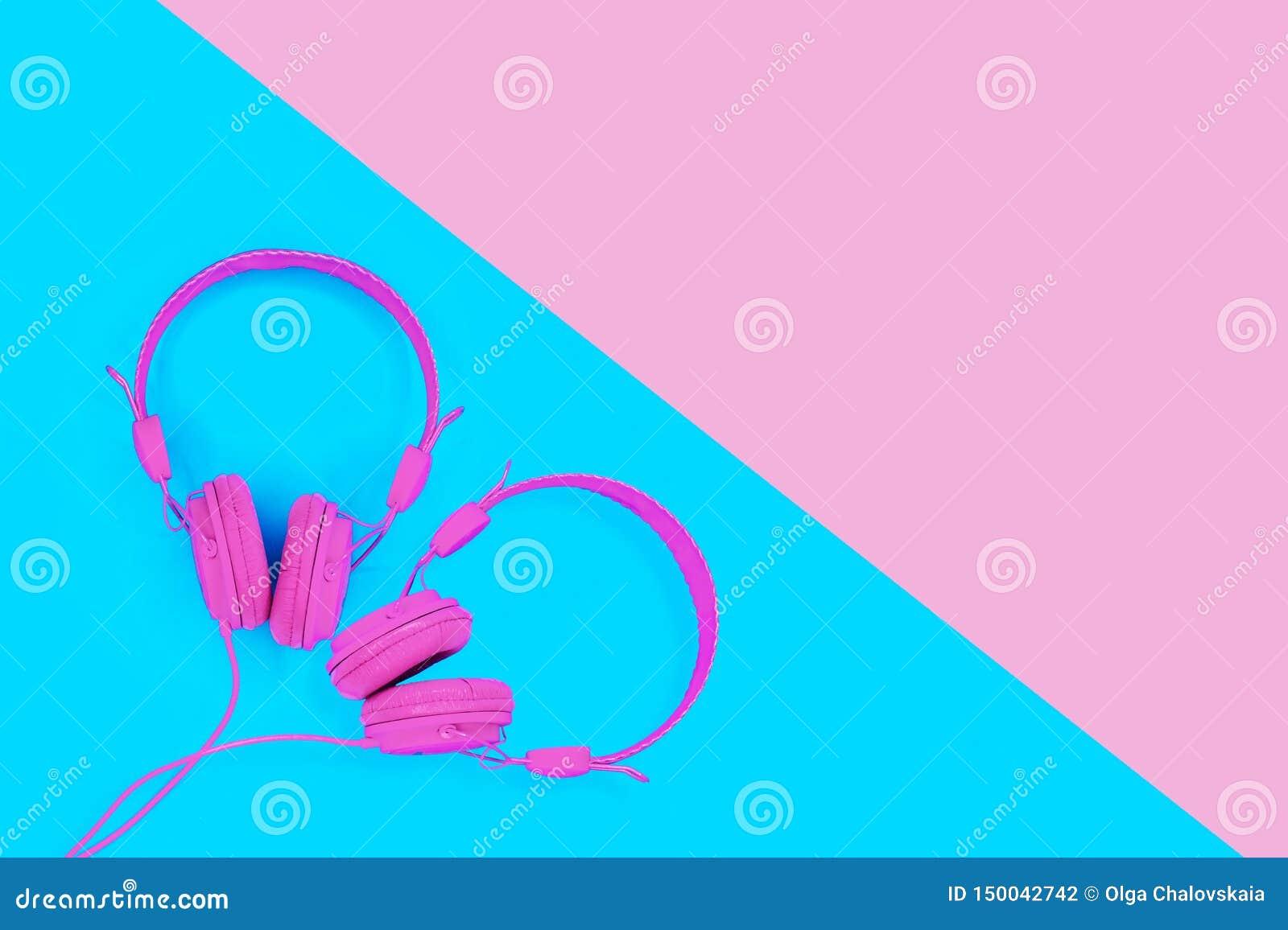 Ett par av rosa hörlurar i formen av en hjärta på blå bakgrund Begrepp för sommarförälskelsemusik med kopieringsutrymme
