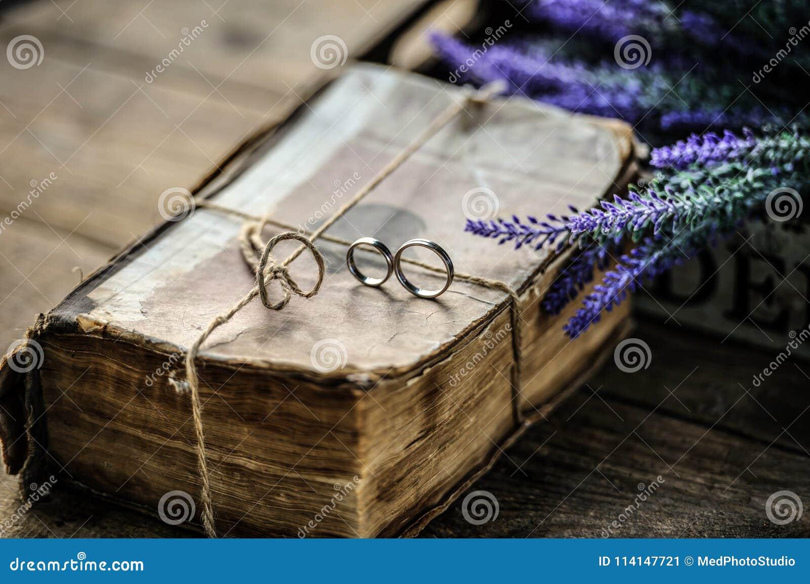 Ett par av vigselringar på en gammal antik tappning bokar