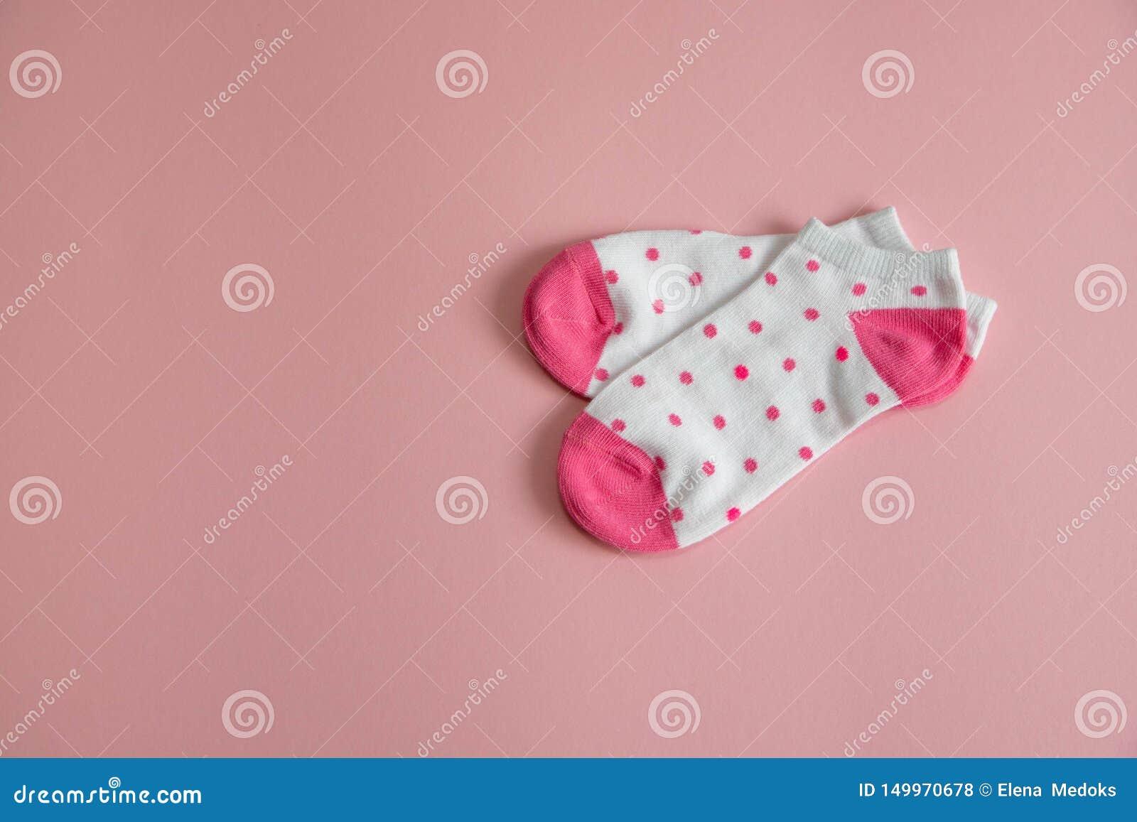 Ett par av vita sockor för barn med rosa sockor och häl, med rosa prickar, på en rosa bakgrund Sockor för flickor