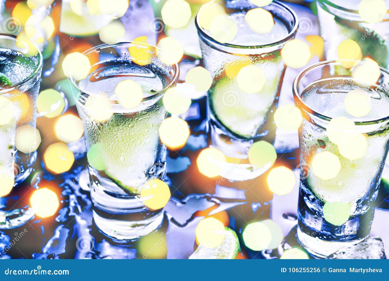 Ett parti i klubban Coctailar på stången _ Vodka, gin, tequila med is och limefrukt Alkoholiserad coctailcoctail selektivt