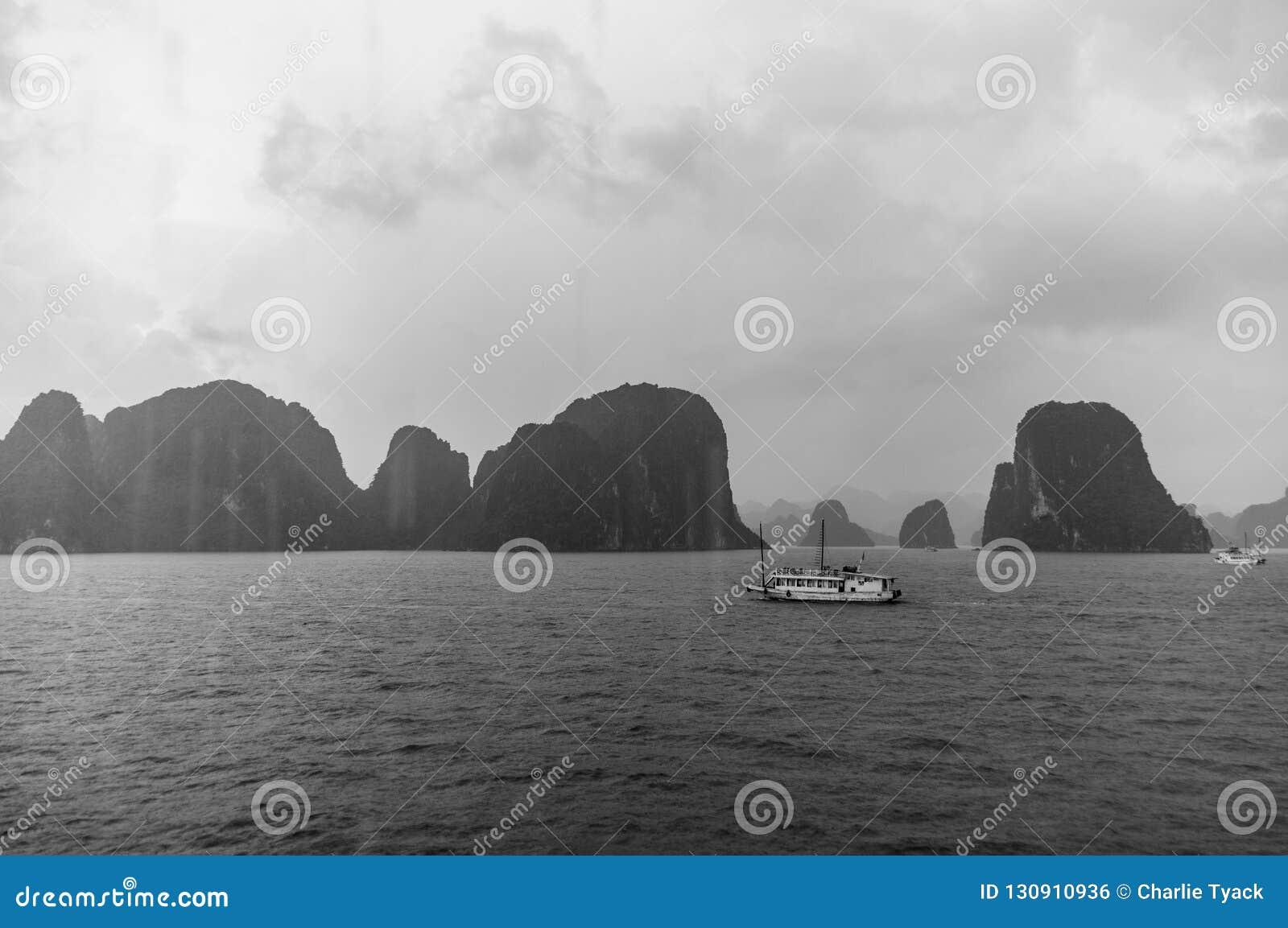 Ett skräpfartyg seglar över mummel den långa fjärden, Vietnam, med regn i förgrunden och mist i avståndet