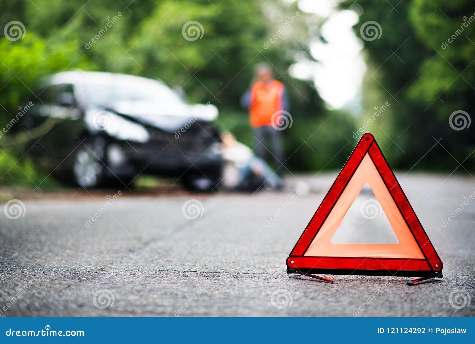Ett slut upp av en röd nöd- triangel på vägen framme av en bil efter en olycka