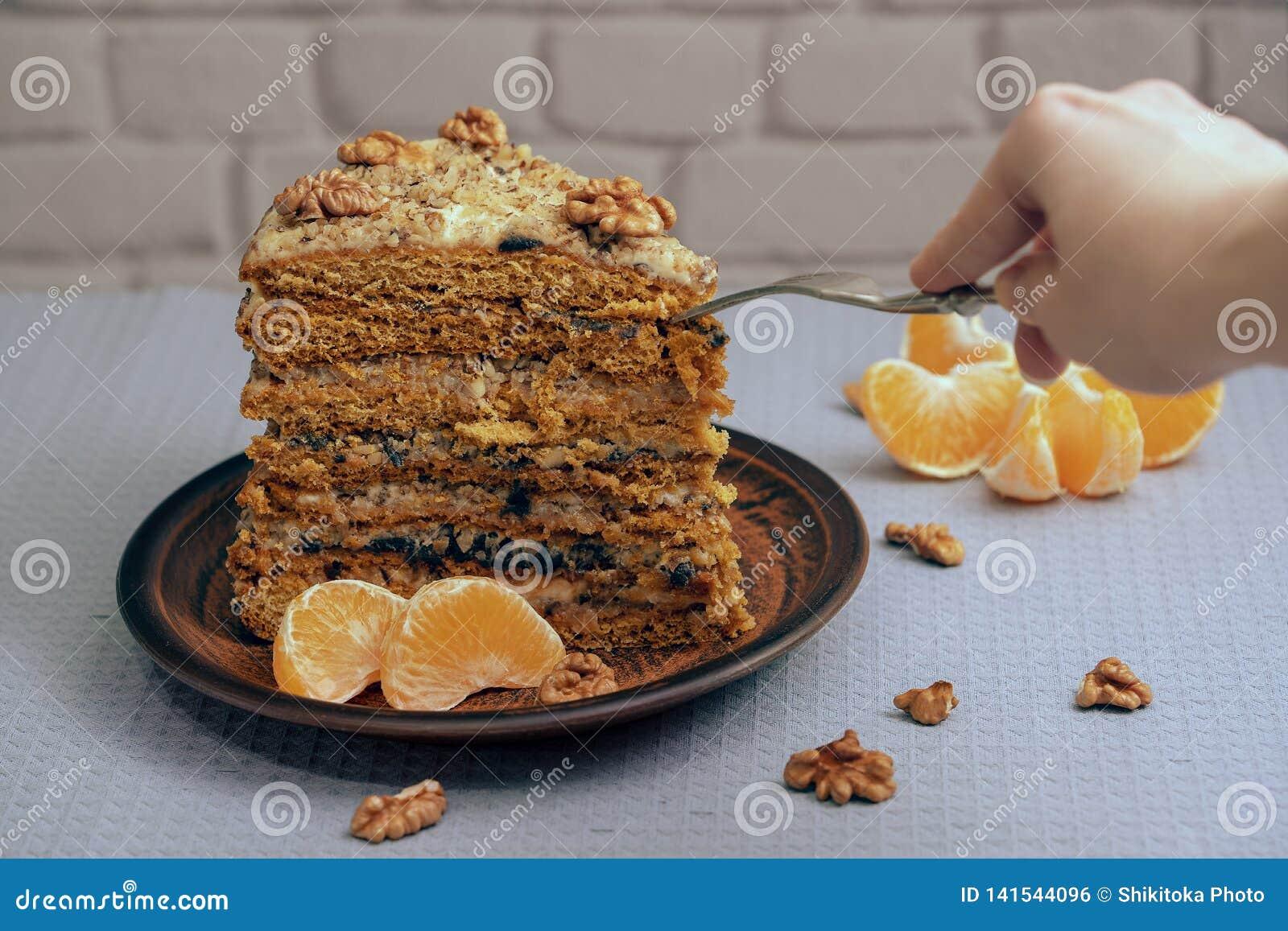 Ett stort stycke av den hemlagade kakan på en keramisk platta med muttrar och mandarinen