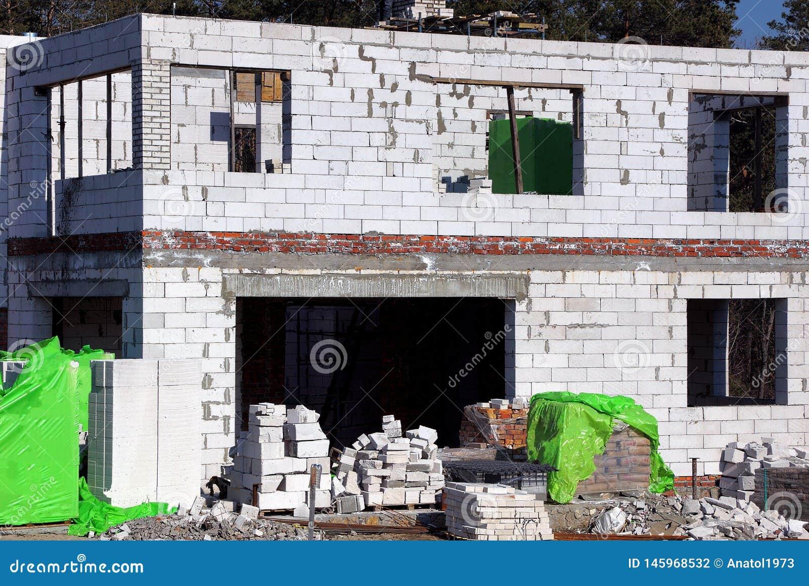 Ett stort vitt oavslutat tegelstenhus på byggandeplatsen