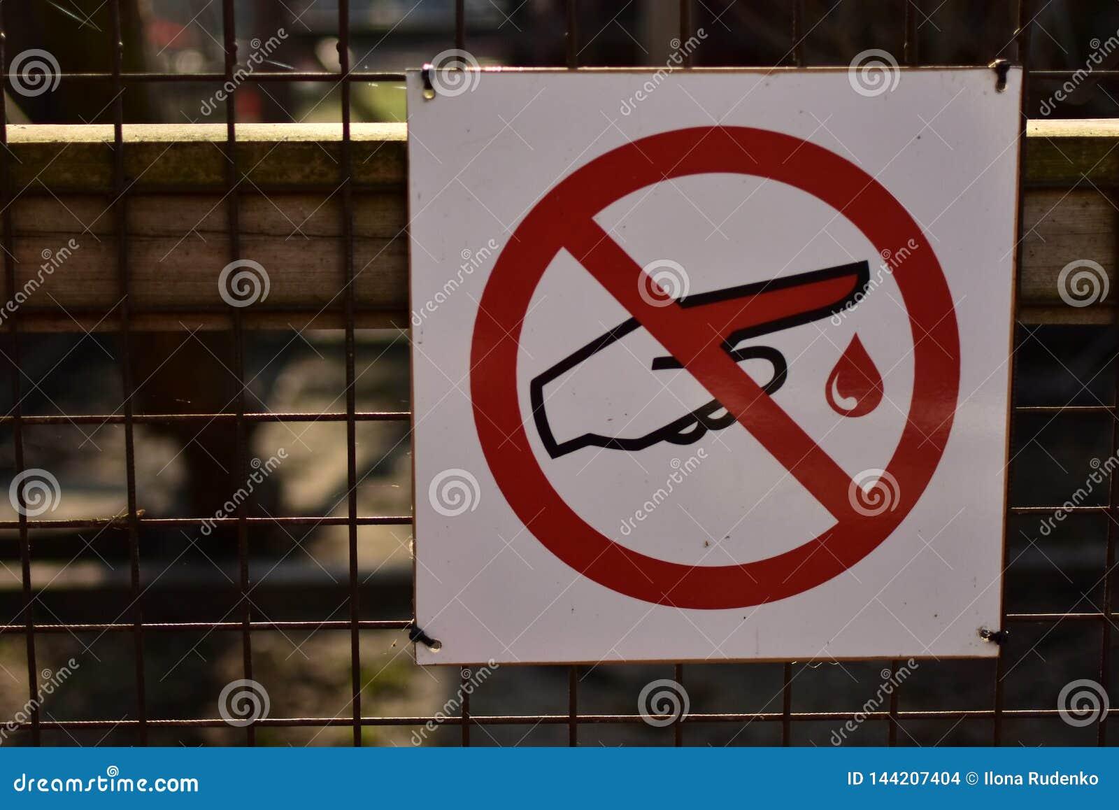 Ett tecken som hänger på ett metallraster som förbjuder för att trycka på det tack vare möjlig fara