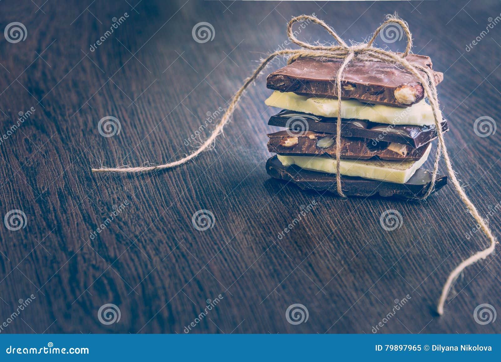 Ett torn av chokladstänger som slås in som en chokladgåva Olika chokladstycken över mörk wood bakgrund