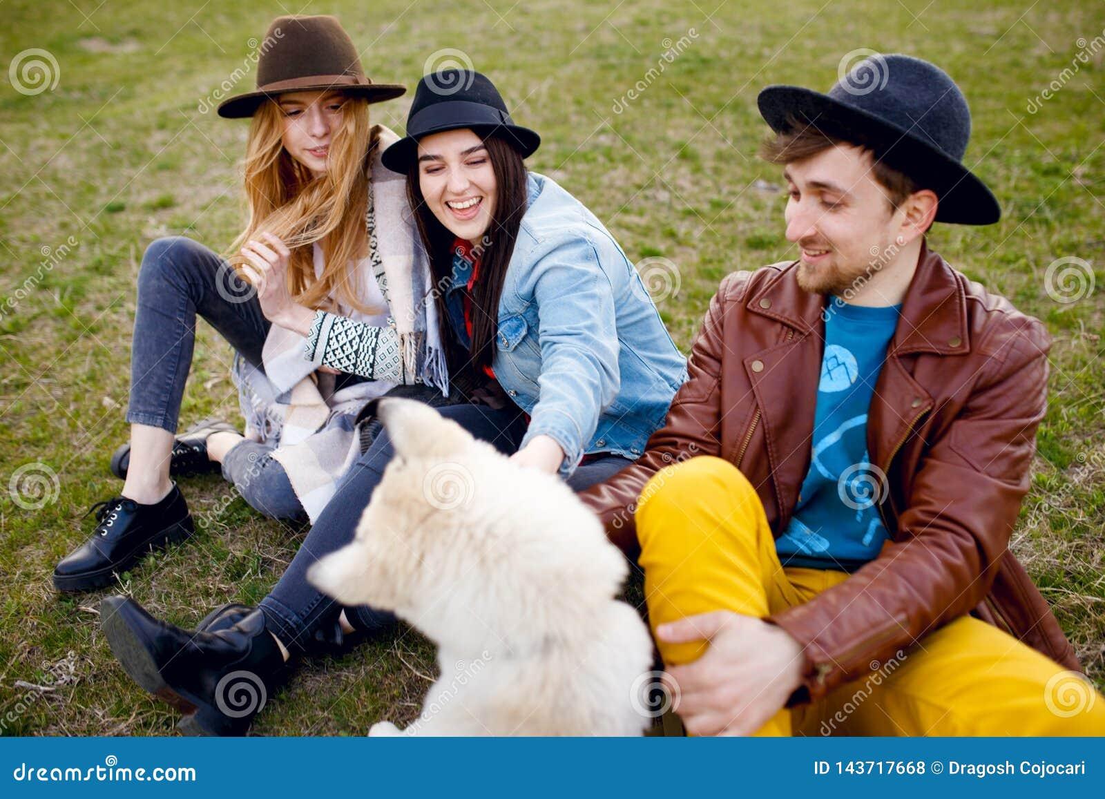 Ett tre ungt stilfullt folk spenderar tid tillsammans utomhus med deras skrovliga hund som sitter på grönt gräs
