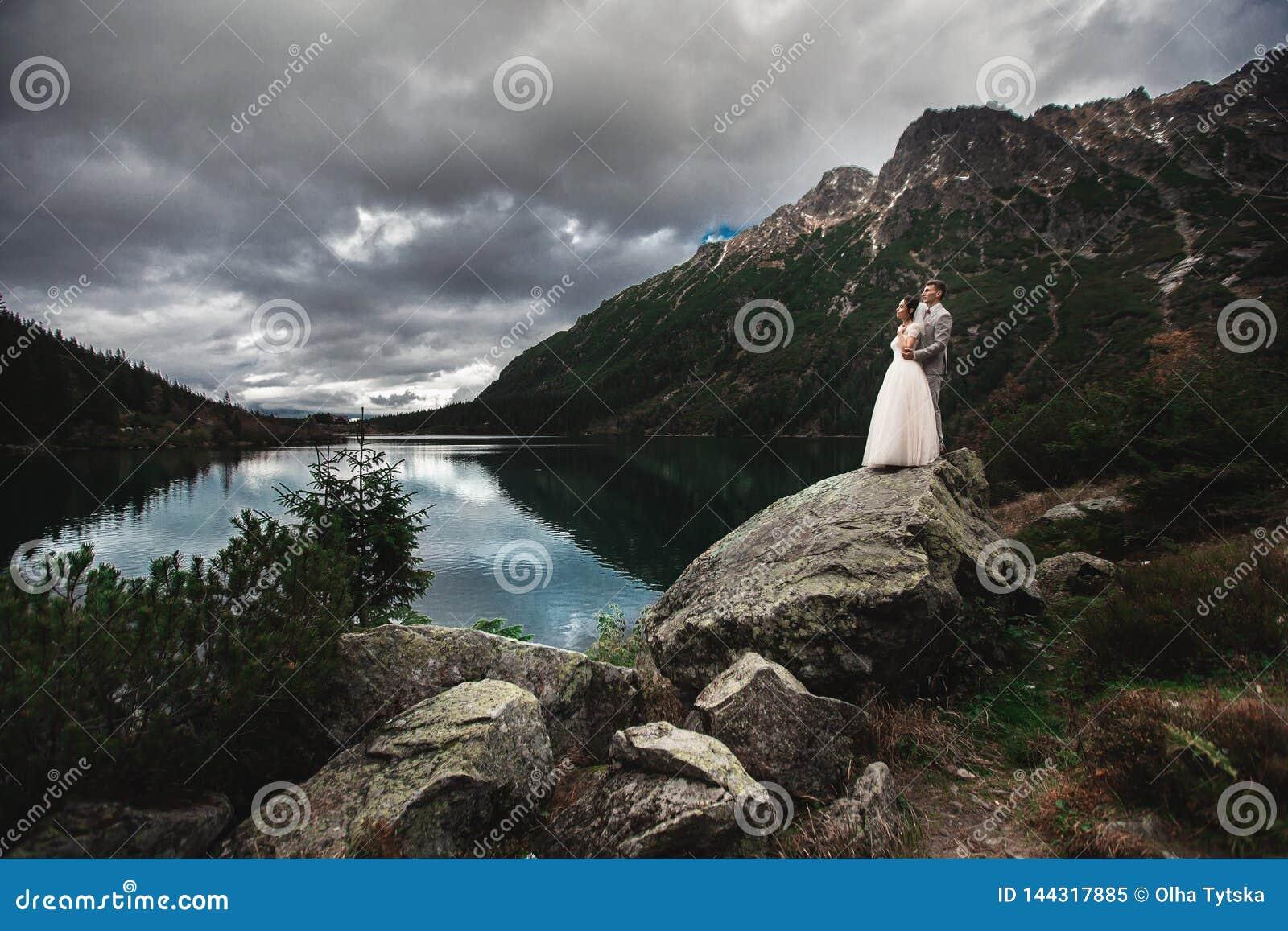 Ett ungt brölloppar tycker om en bergsikt på kusten av en sjö Morskie Oko