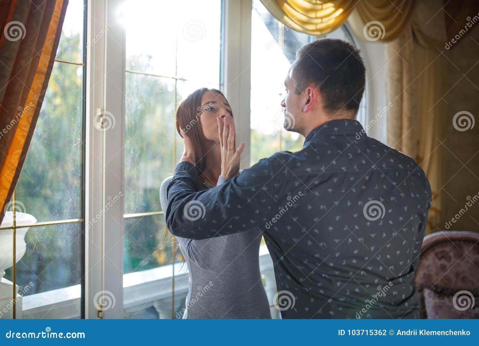 Ett ungt gift par grälar i ett modernt hus vid fönstret