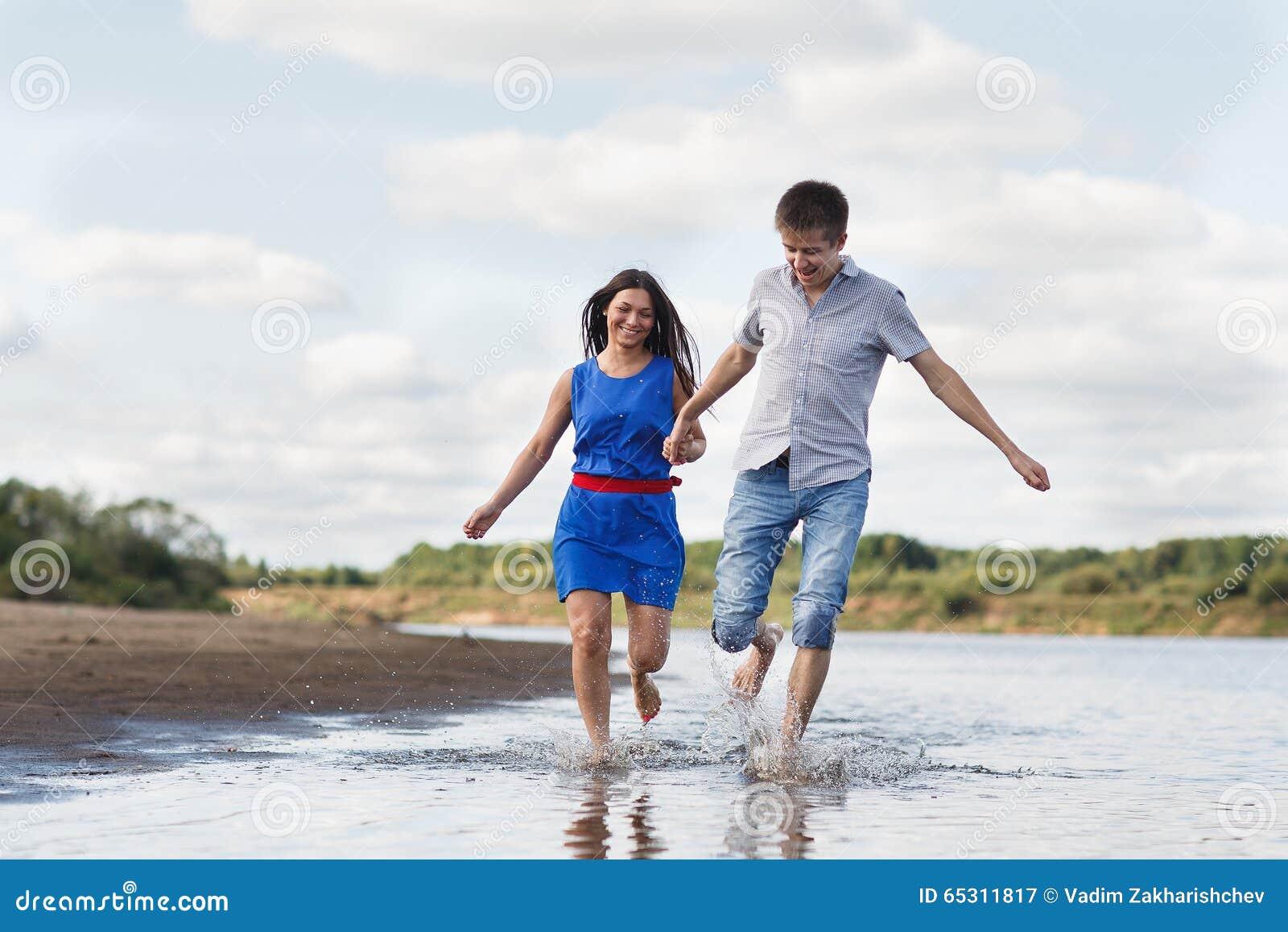 Ett ungt par promenerar stranden