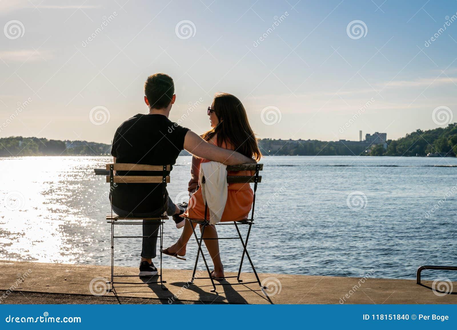 Ett ungt parsammanträde på stolar på en kaj av vattnet som ser solnedgången