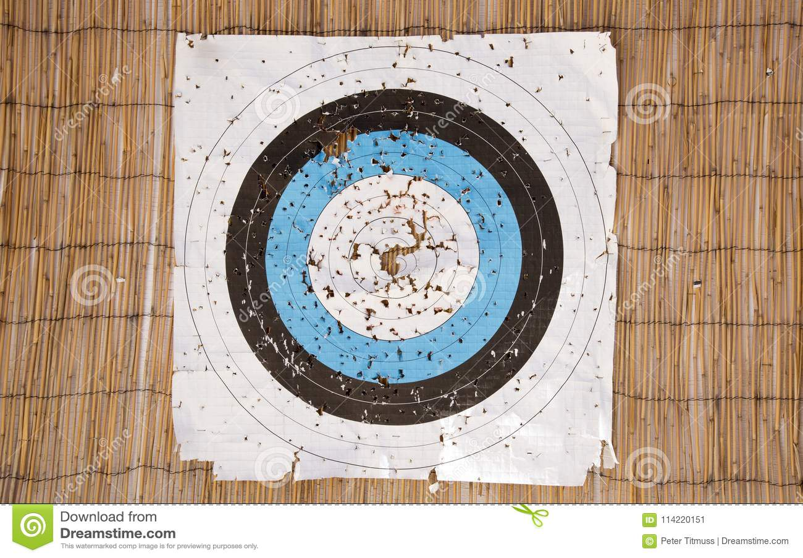 Ett väl använt bågskyttepappersmål med massor av hål