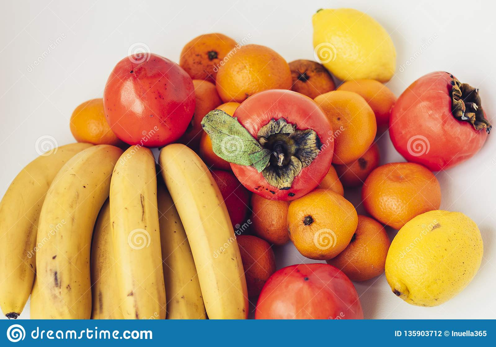 Ett val av ordnade olika nya frukter av bananer, mandariner, persimoner och citroner på det vita bakgrundsslutet upp