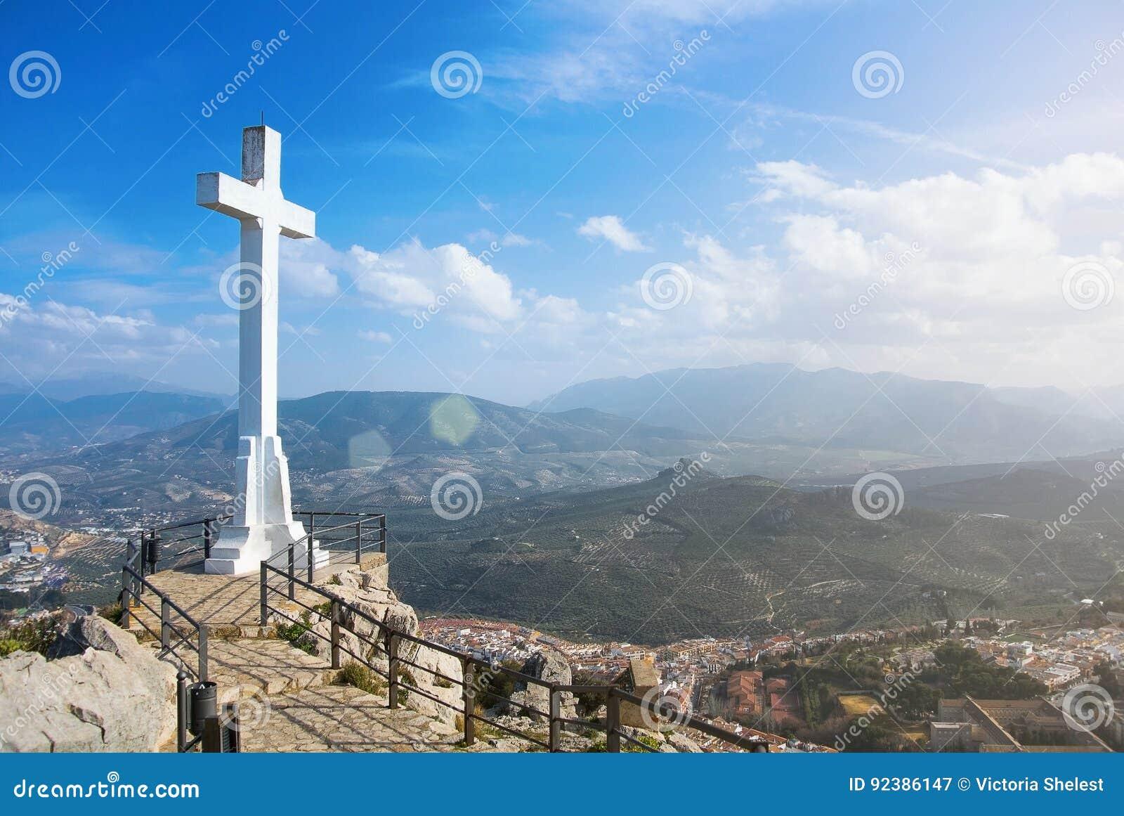 Ett vitt korsar över den Jaen staden på berget, ett symbol av staden med toppiga bergskedjan Magina berg på bakgrund på solig dag