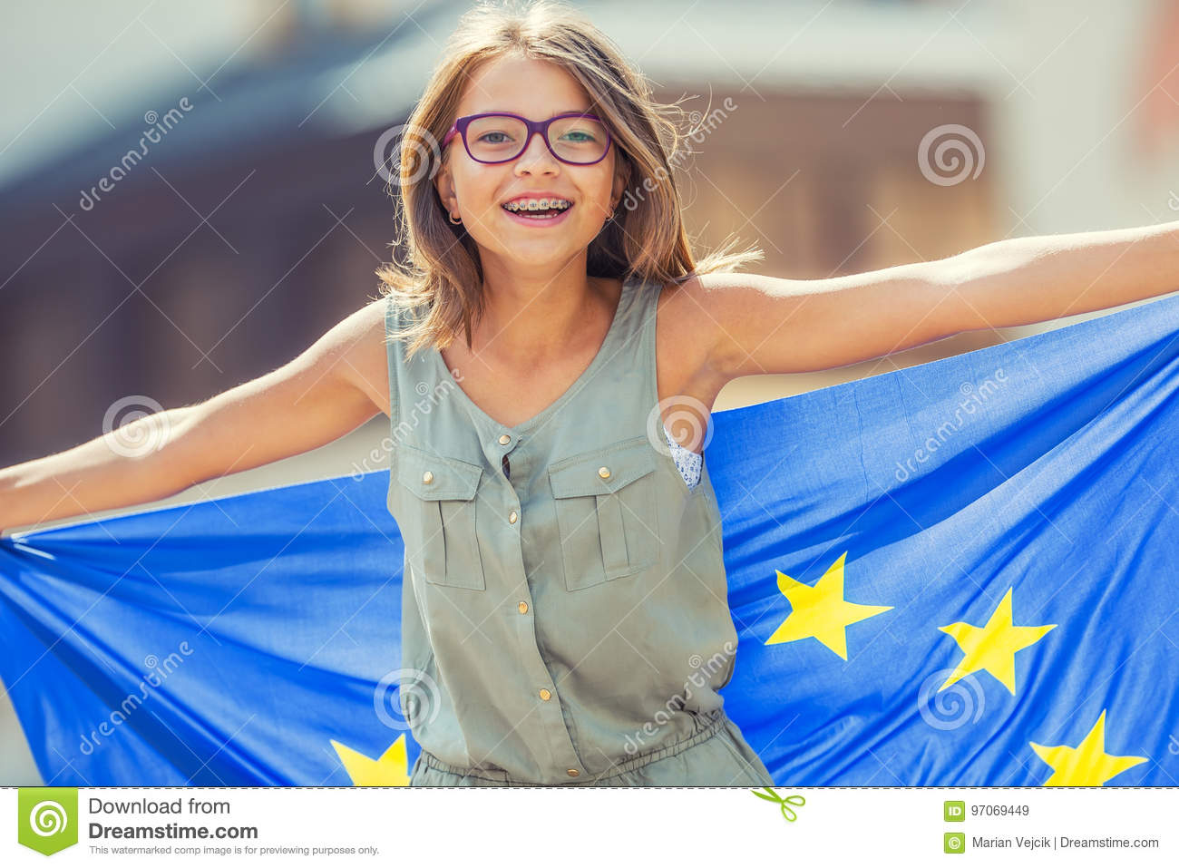 EU Flag. Cute happy girl with the flag of the European Union. Young teenage girl waving with the European Union flag in the city