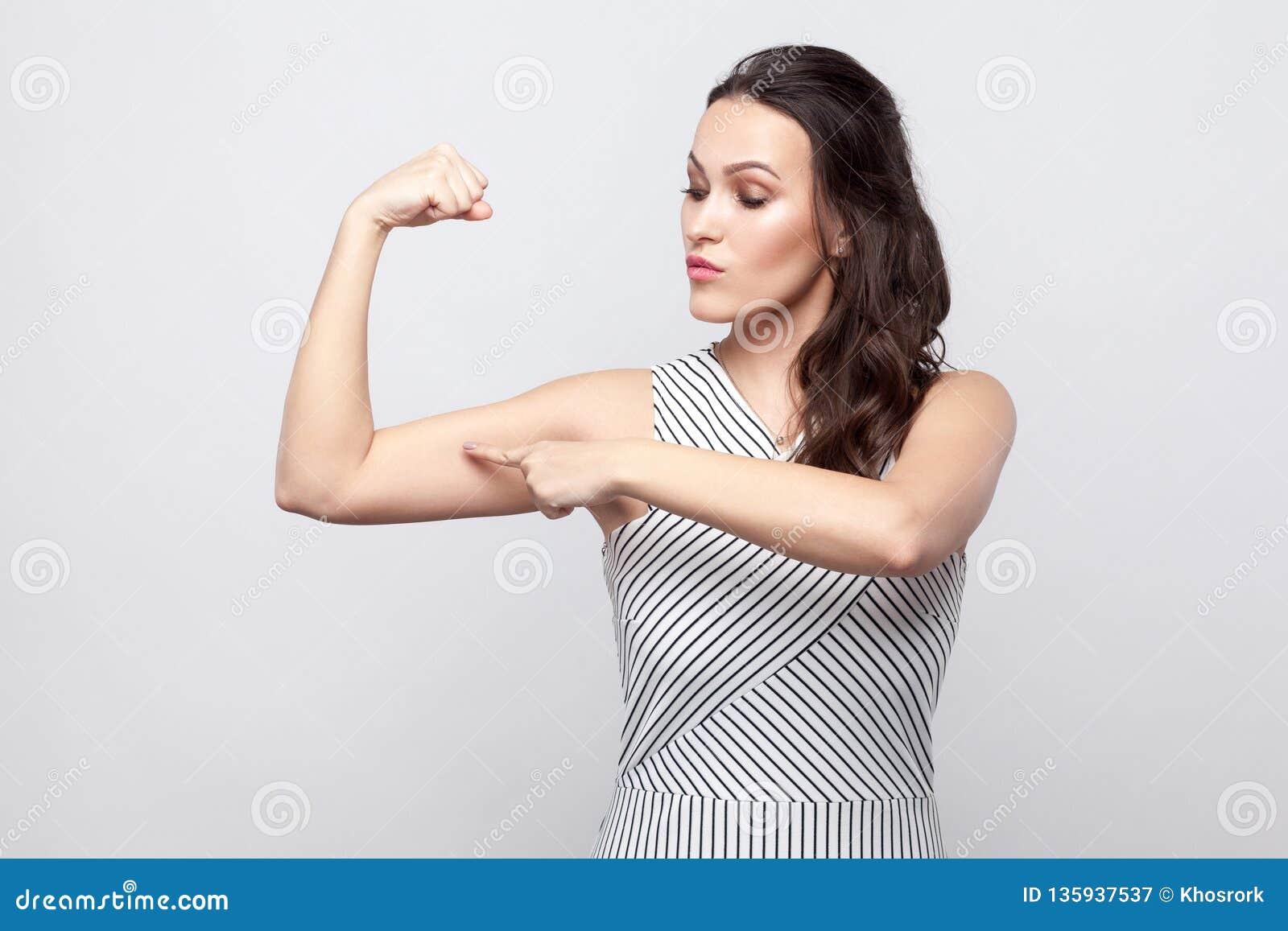 Eu sou forte Retrato da mulher moreno nova bonita orgulhosa com composição e posição listrada do vestido e apontar em seu bíceps