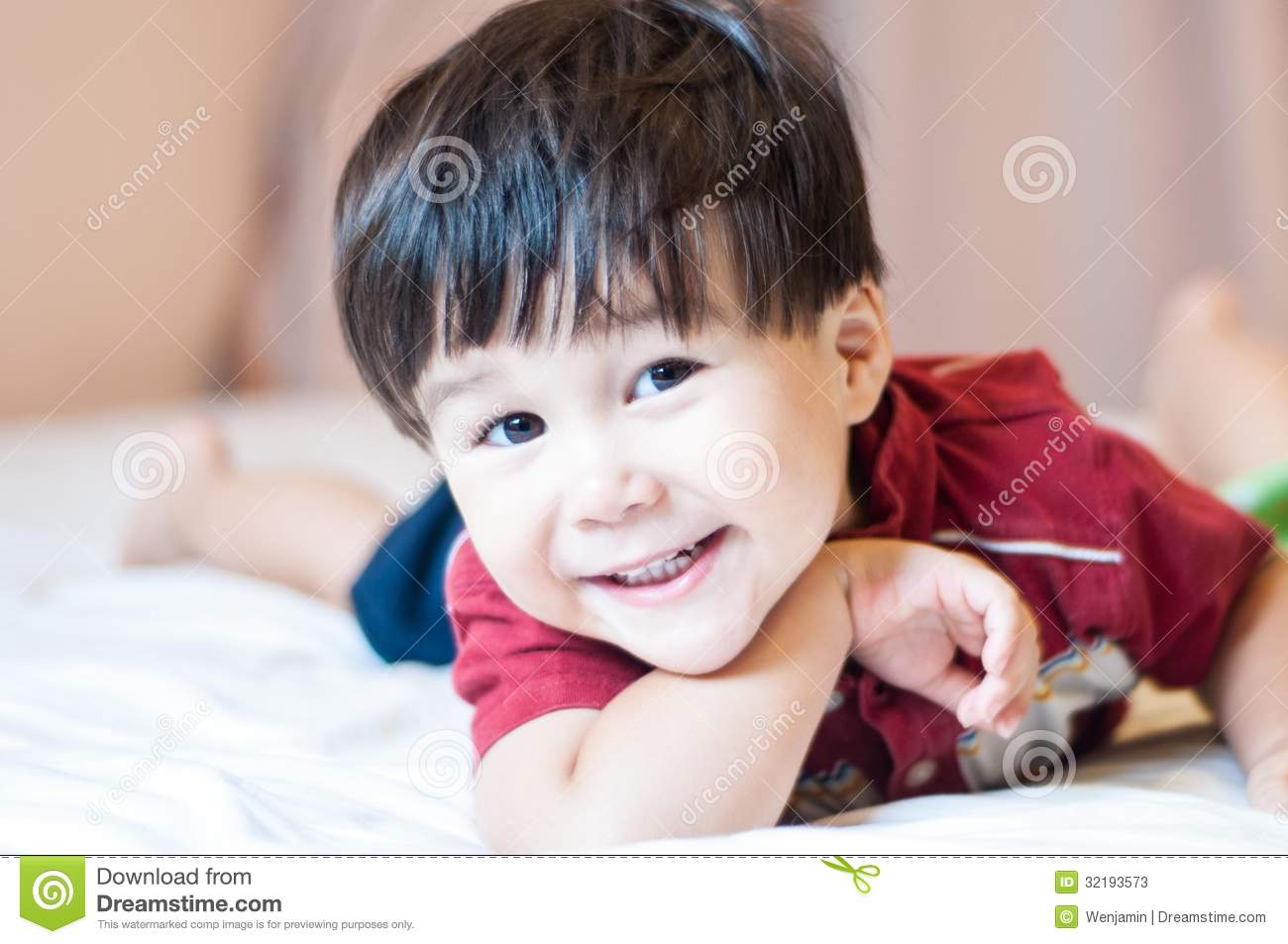 Eurasian Toddler Boy Smiling On A Bed Stock Photos