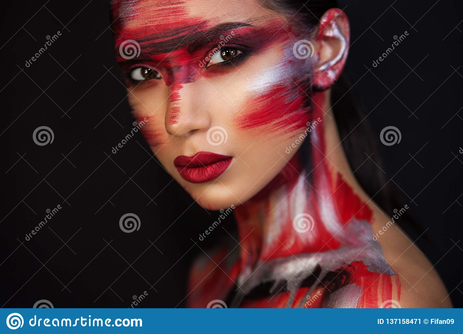 The Euro-Asian woman looks directly at us, on a black background, sensual red lips are closed, red silver black makeup emphasizes her image